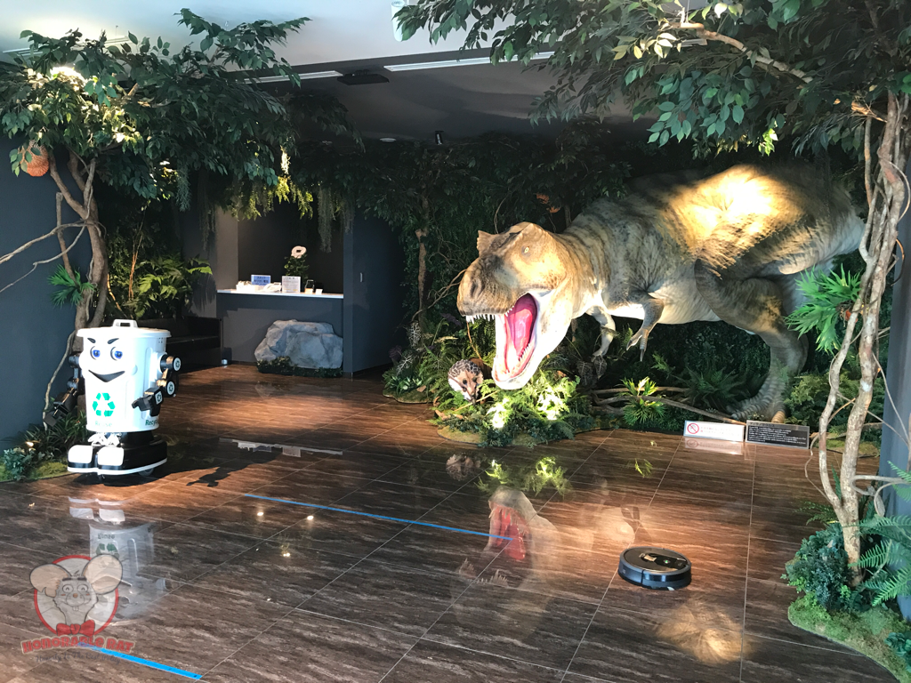 A robot cleaning the floor, a trash bin and a photo opportunity with T-Rex
