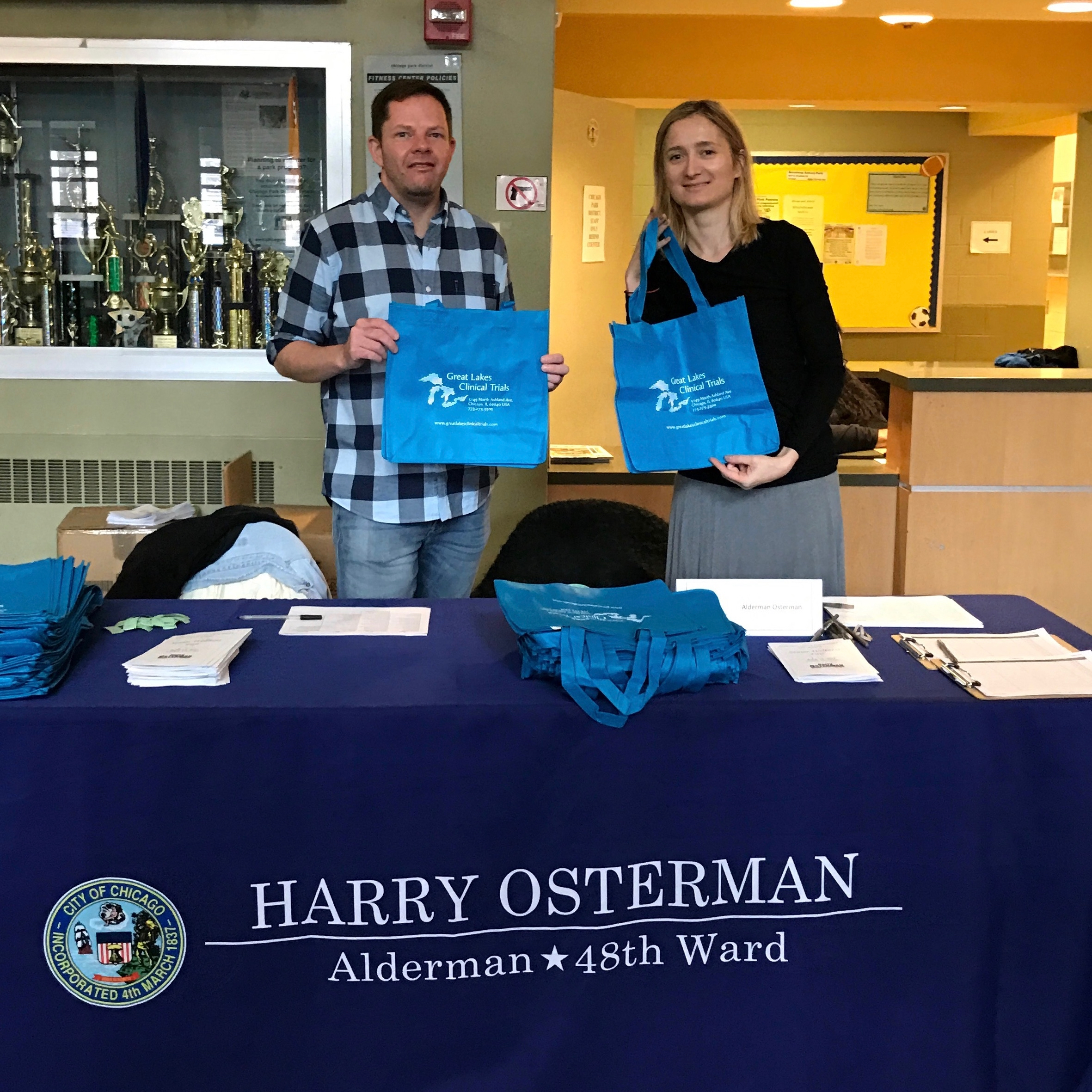 Representatives of Alderman Osterman pass out Great Lakes Clinical Trials canvas grocery bags