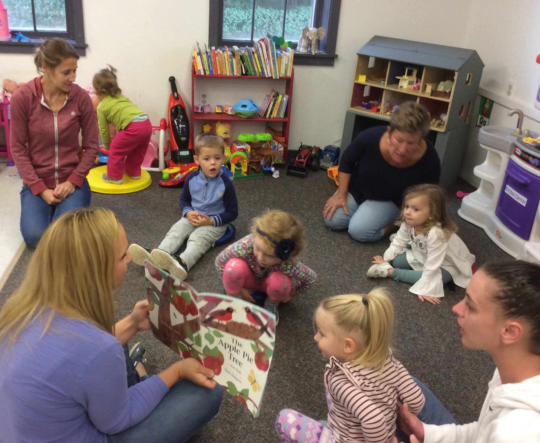 The Family Foundation 5 kids and adults are engaged with Jennifer Gagnon as she reads The Apple Pie Tree book.