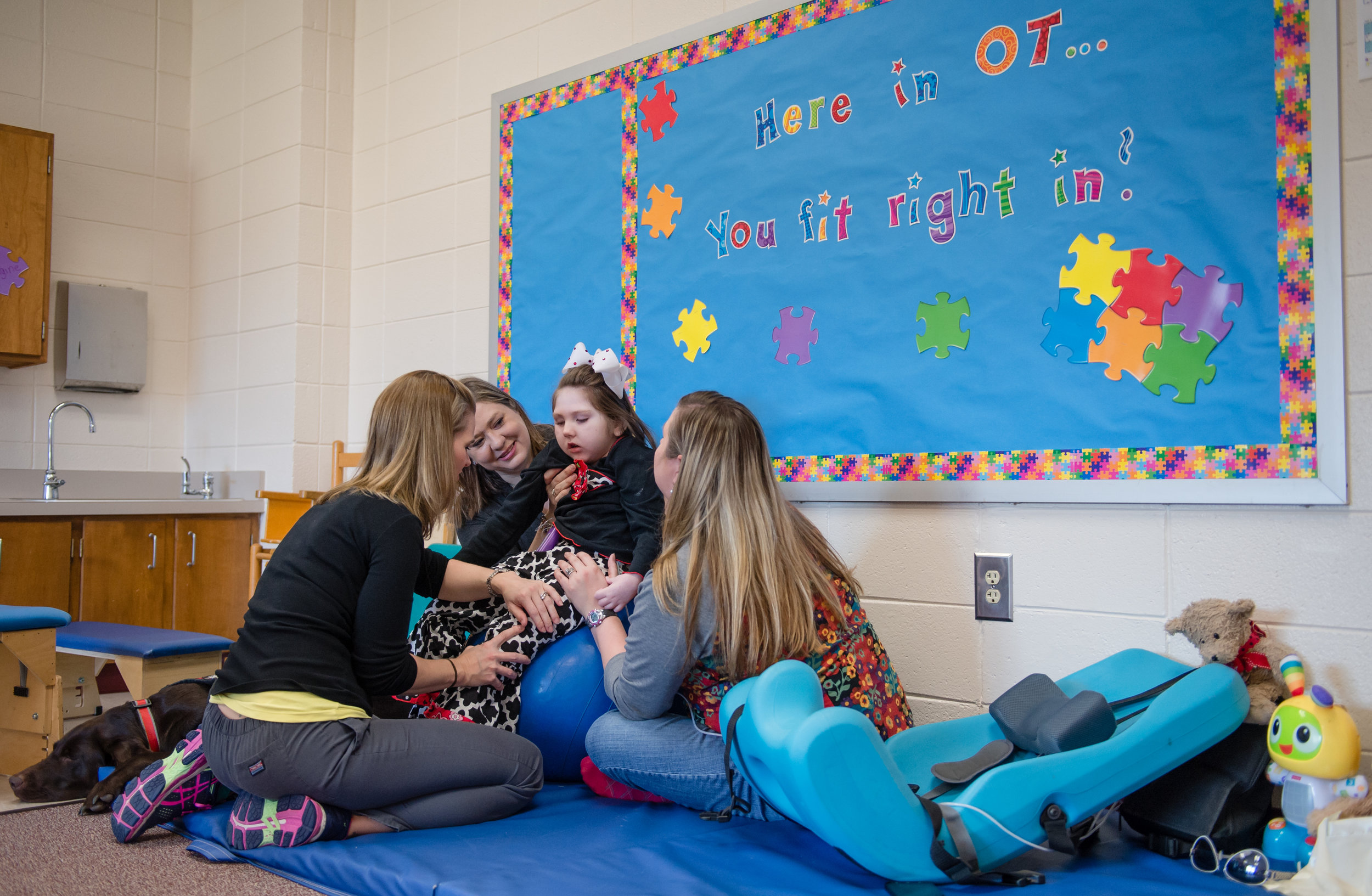 Haleigh receives therapy from (from left) physical therapist Julie Sullens, mom Janea and certified occupational therapist assistant Rachel Meeks at Hubbard Elementary School in Forsyth, Ga. Haleigh's service dog Kala (seen far left) never strays far from Haleigh's side.