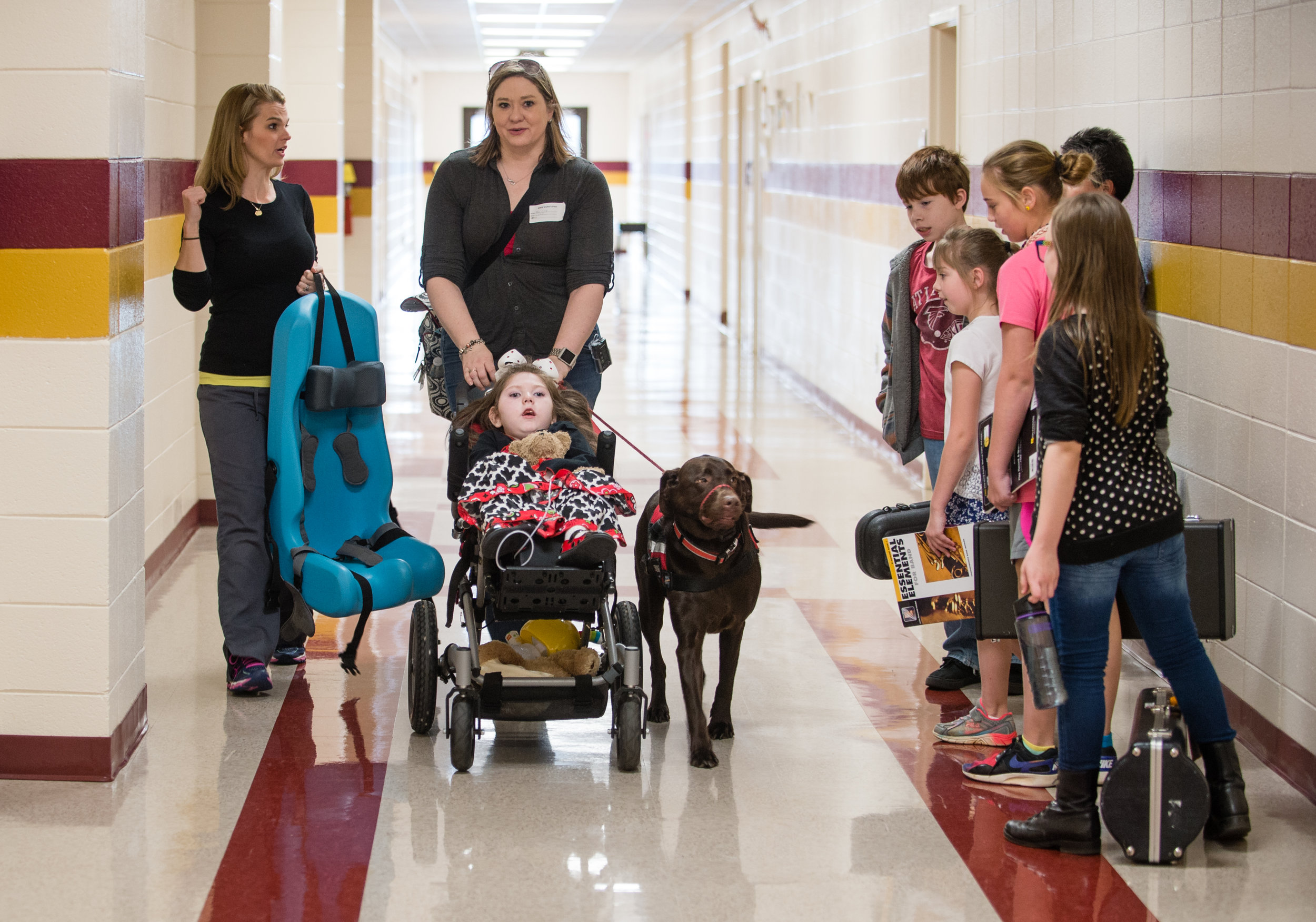 Janea pushes Haleigh and walks with physical therapist Julie Sullens down a hallway at Hubbard Elementary as they leave one of two weekly physical therapy sessions at the school.