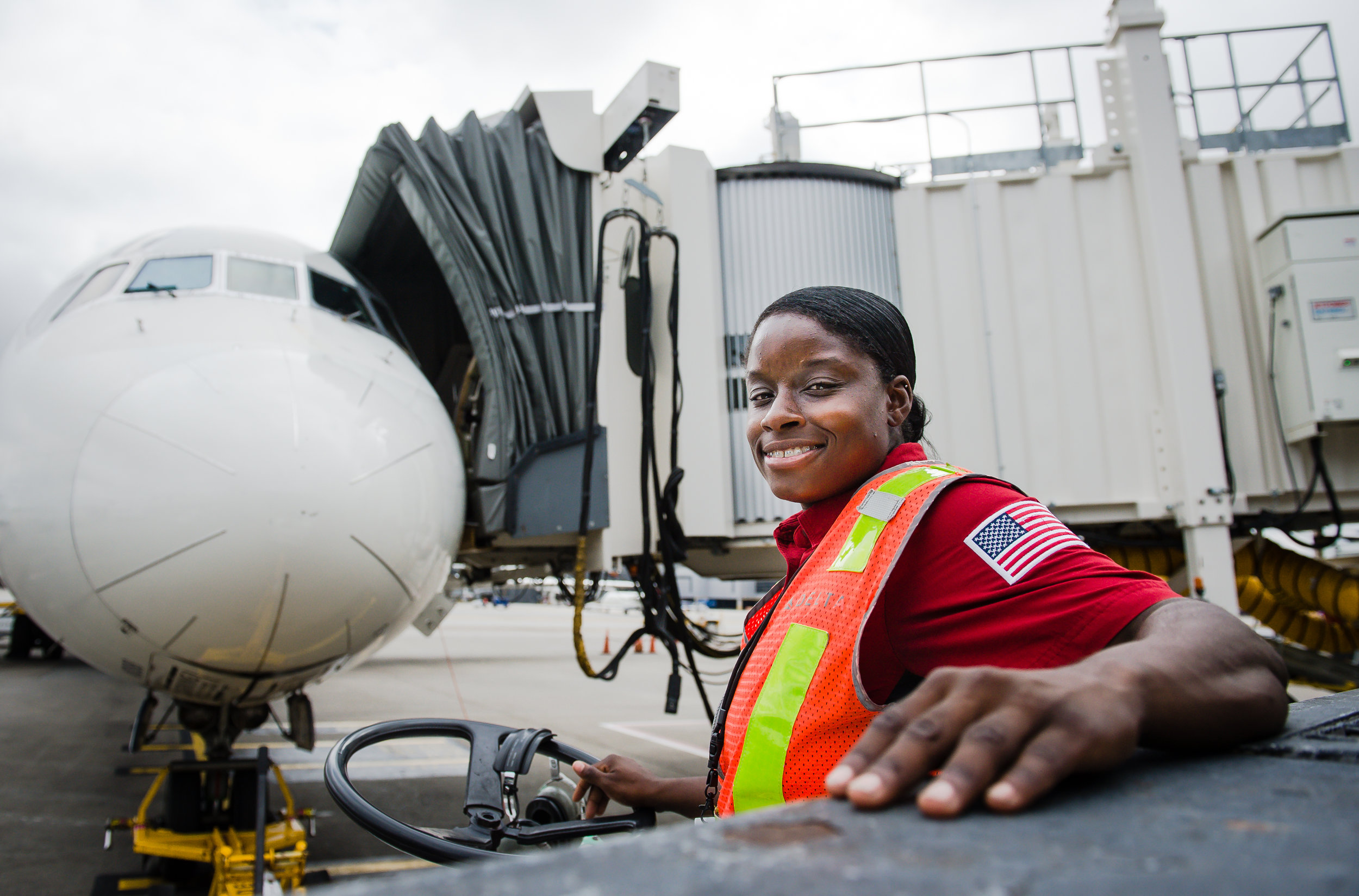 Charlessa Brightwell, a Delta Airlines Aircraft Load Agent, poses for a photo after connecting a pushback tug to the aircraft shown in preparation for takeoff at Hartsfield Jackson Atlanta International Airport Friday, 28 Sept. 2018.