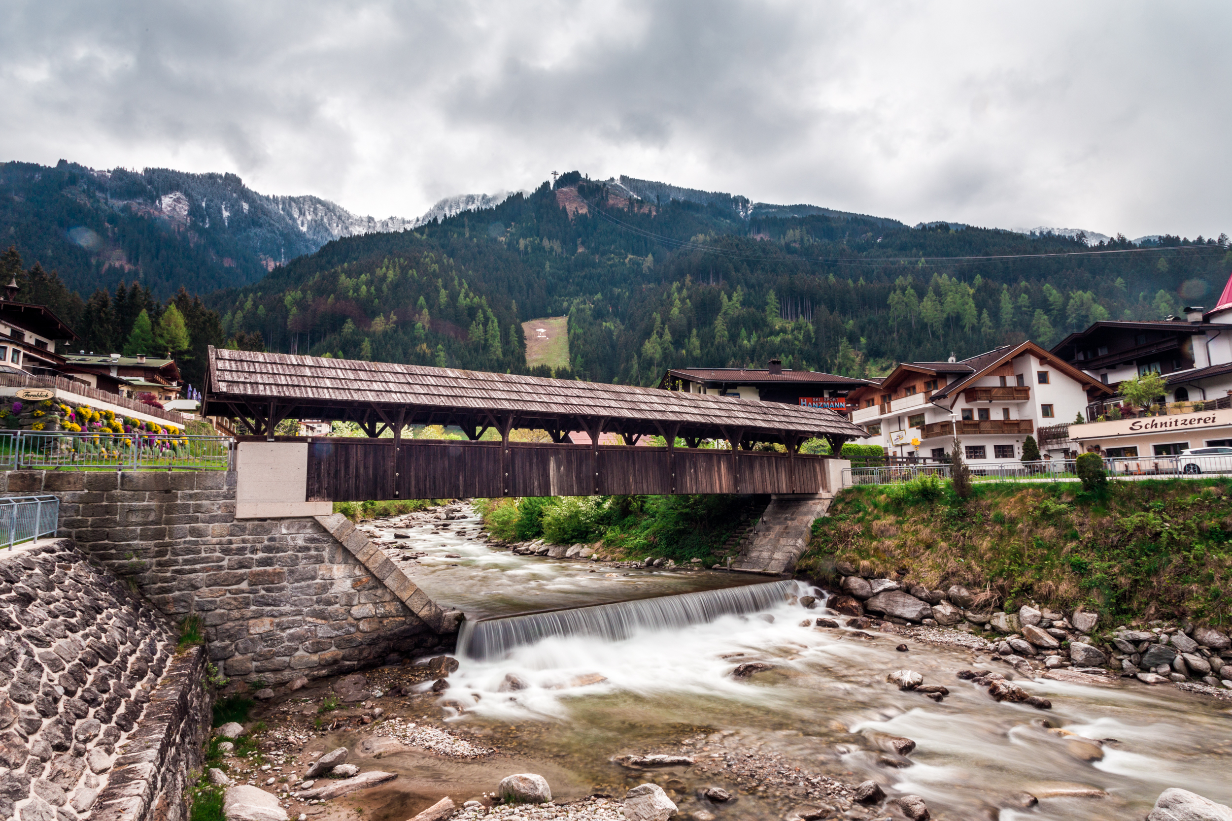 This is a classical Austrian footbridge with the roof, with the Ahorn Mountain in the background.