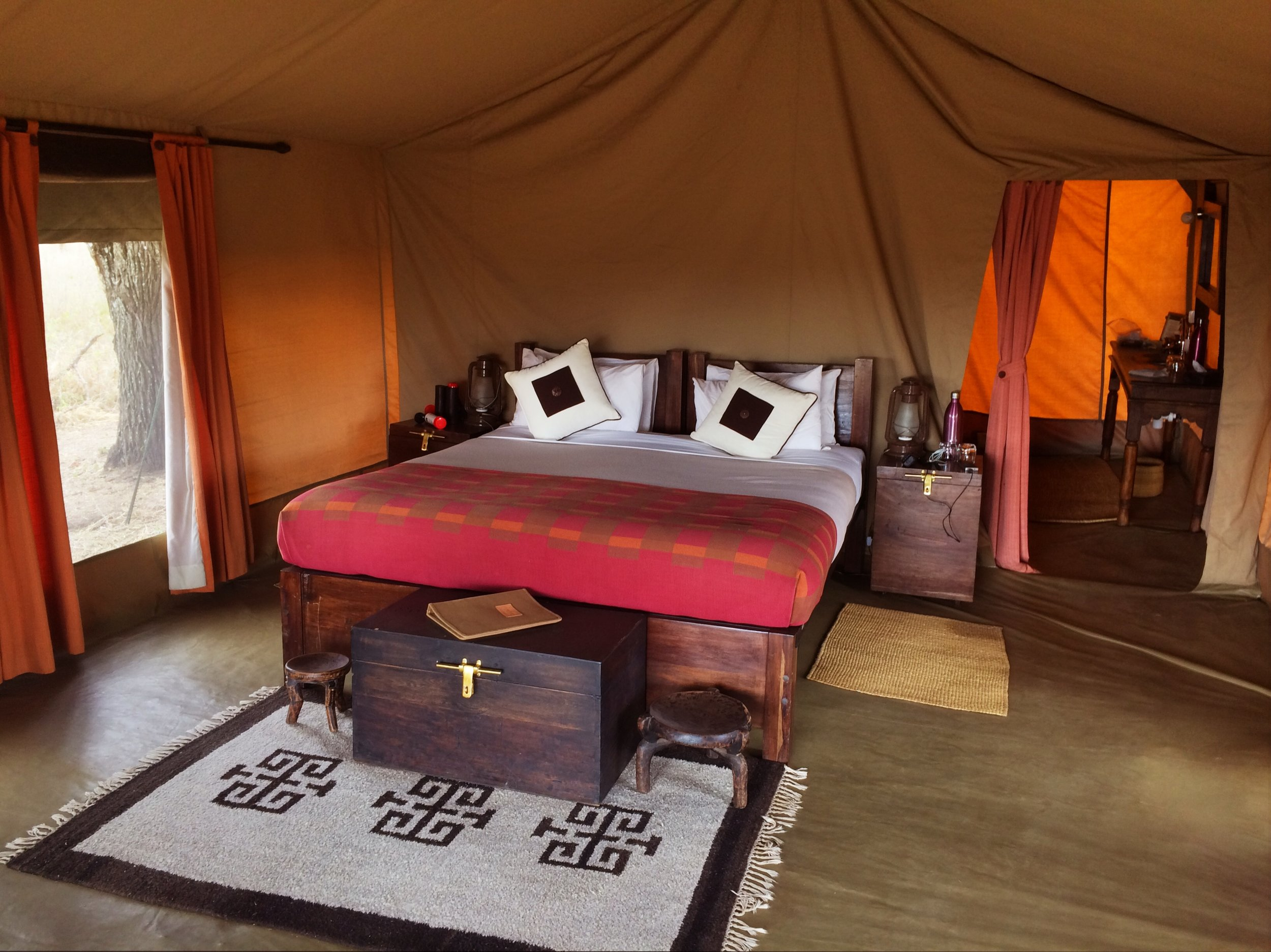 "Inside my tent at Dunia Camp. En suite bathroom with ""camp shower"" located in the back."
