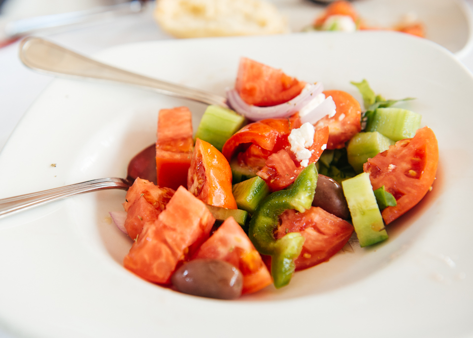 Greek salad with fresh tomato, peppers, feta, and olives.