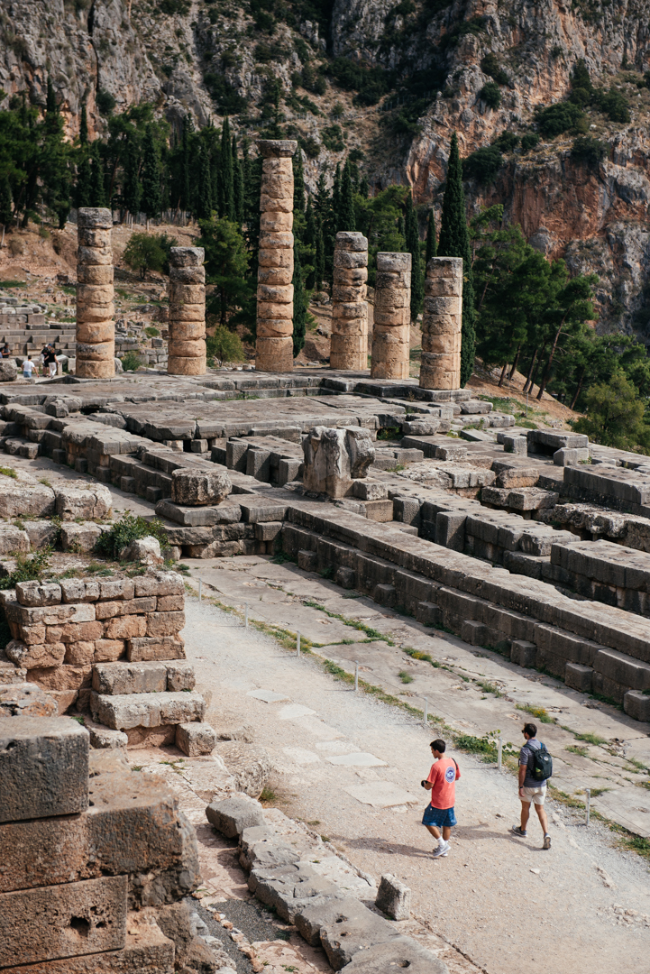 Students walk along the courtyard towards the columns of the Temple of Apollo.