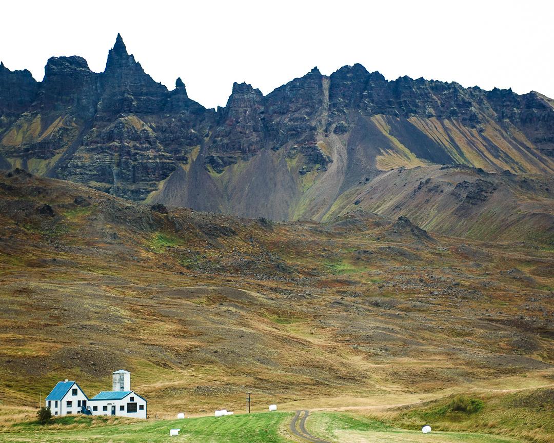 Farmhouse sits below a rugged mountain range.