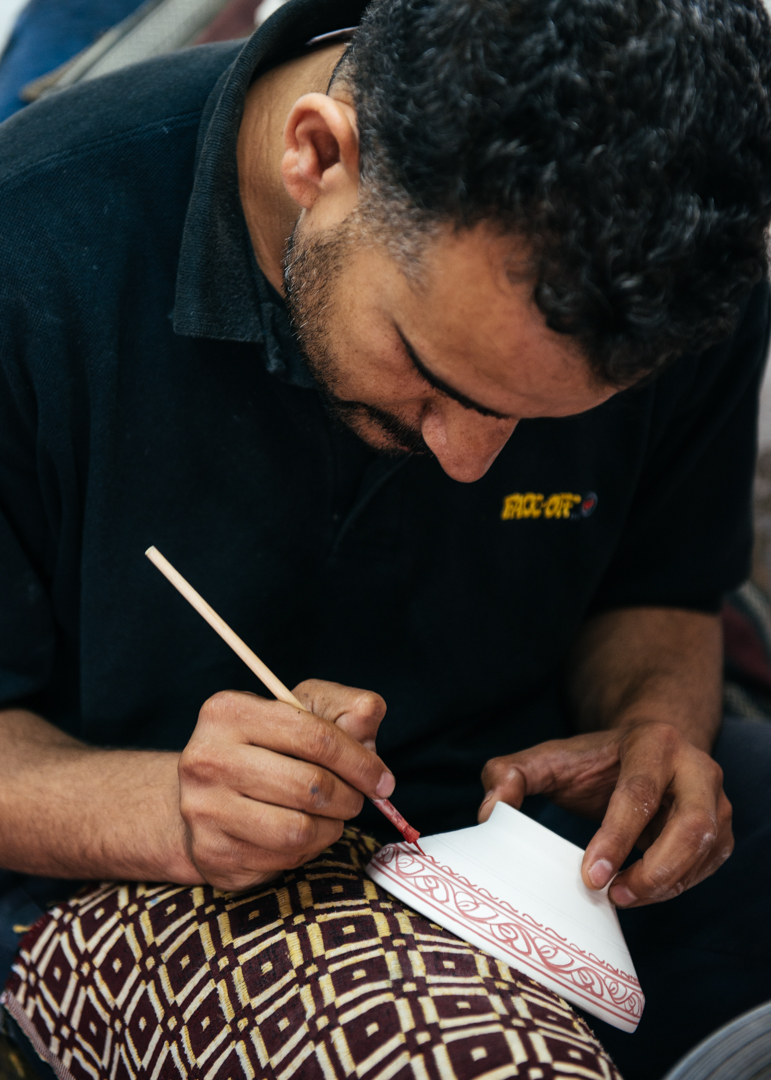 hand painting a pattern on a bowl.