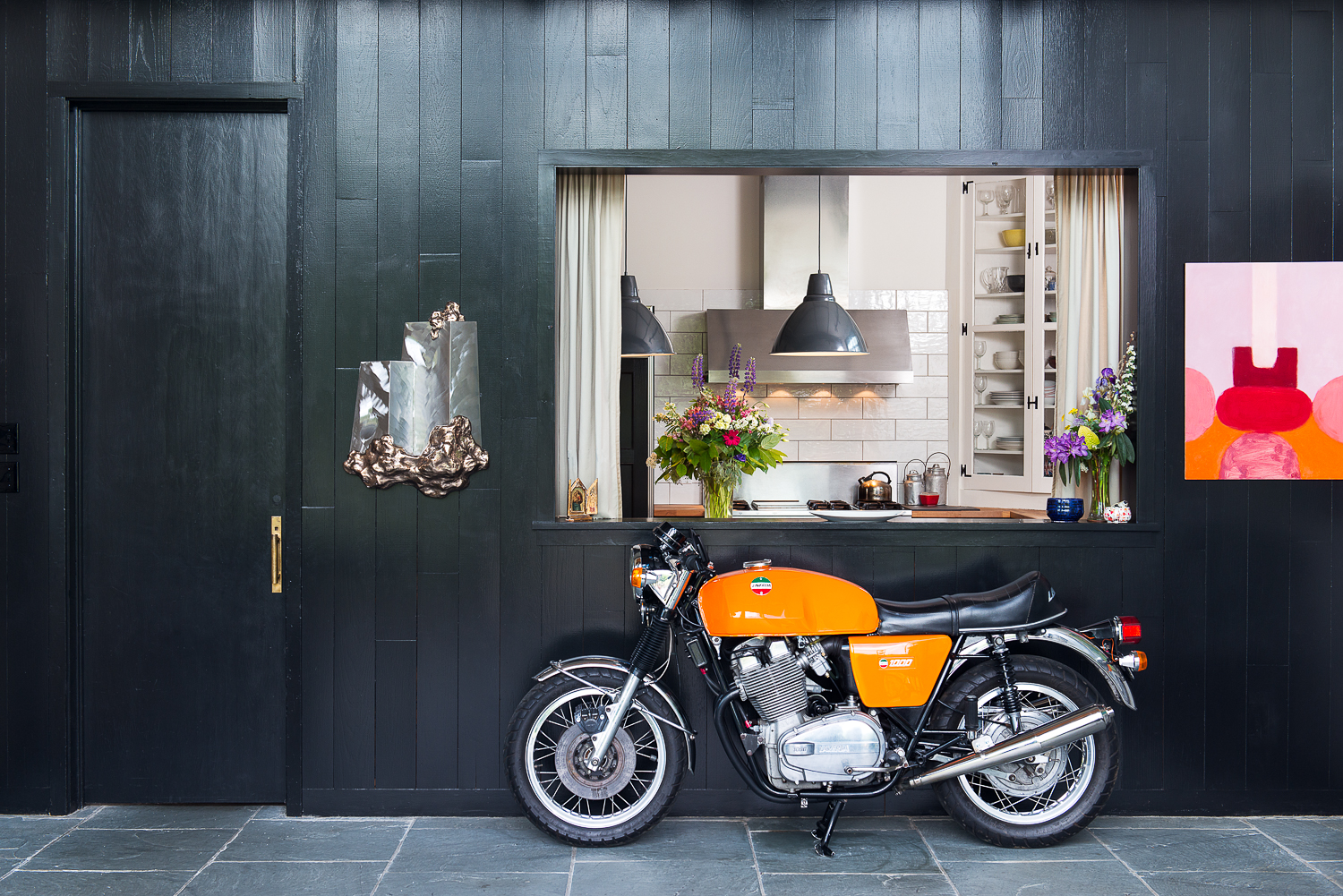 Entryway looking into the kitchen with a classic Laverda 1000 motorcycle.