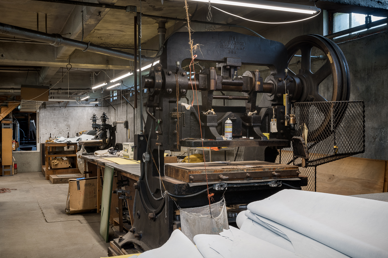 Industrial press is used to cut through multiple layers of fabric. Its original use was for cutting newspaper.