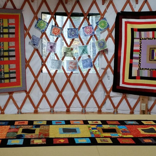 Hanging quilts and prayer flags in our yurts. Getting ready for November exhibit and sale. Saturdays and Sundays. Quilts by Ellie Fellers and flags by Sharon Vandermay. #quilts#prayerflags#yurts#newgloucestet#norumbega