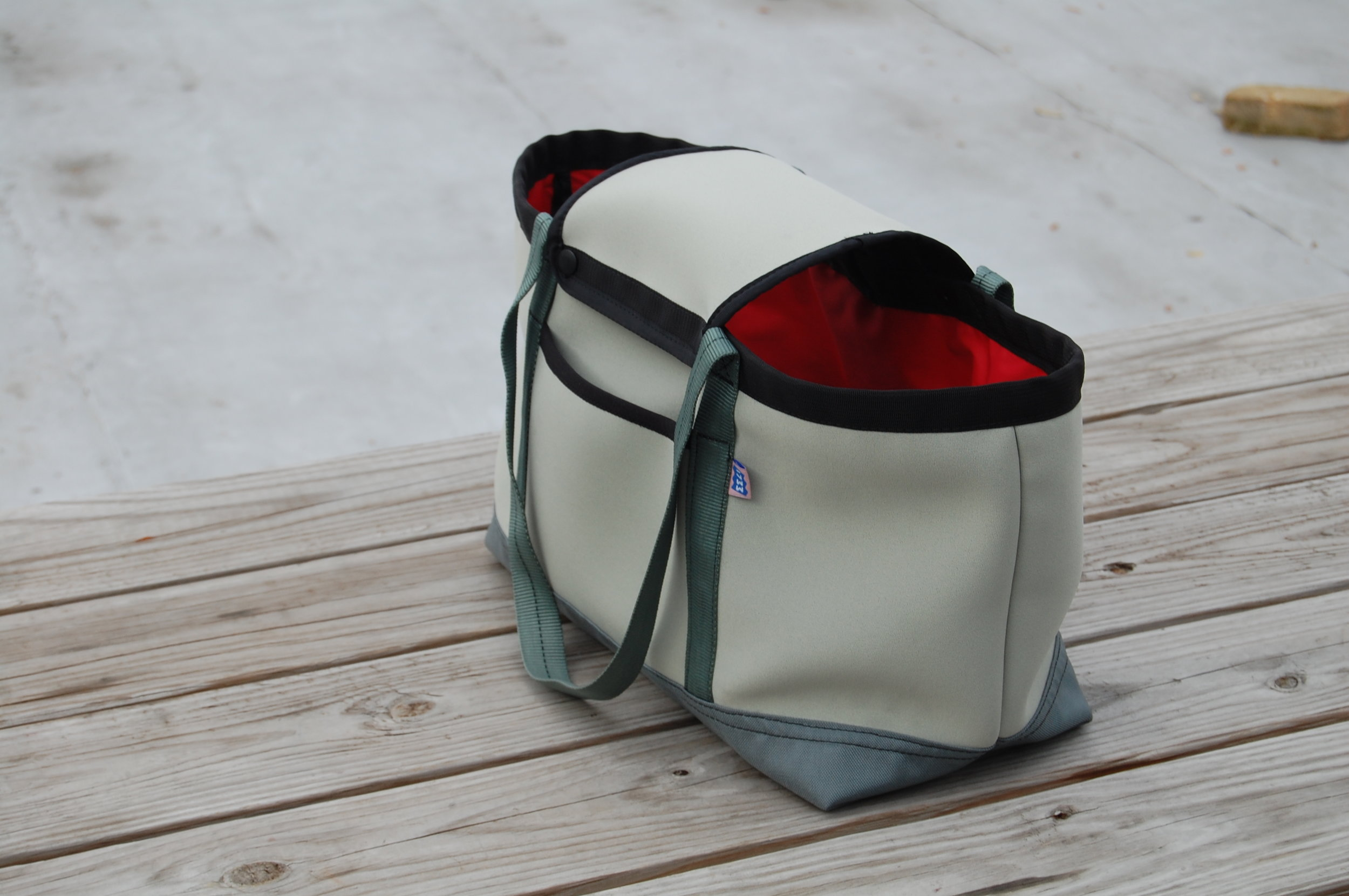 Neoprene tote with a detachable lid designed for carrying a dog.