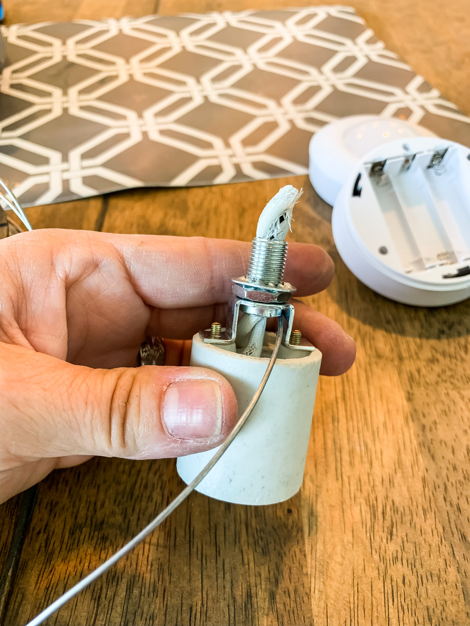 Thread flexible wiring through the top of the thing that holds the lightbulb and loop it around the bottom, where the lightbulb would go.