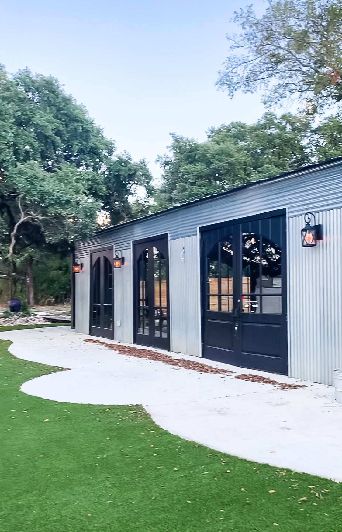 The exterior of the barn, with more of Willie's doors. I love the cute curved foundation! That's astroturf, not real grass.