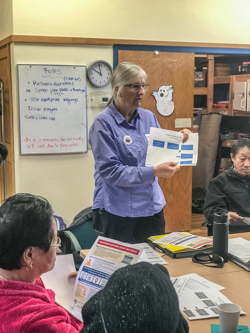 Ingrid Rothe, co-chair of the Dane County Voter ID coalition, uses a fact sheet developed by LWV Wisconsin to explain what the Wisconsin Supreme Court is and what Justices do.