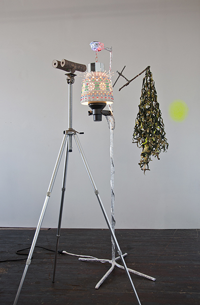 Kim Jong Un with Camo Net and Disembodied Glow  Tripod, Branches, Mirrors, Lamp, Aluminum Tape, Pigment, Acrylic, Fabric, Collaboration