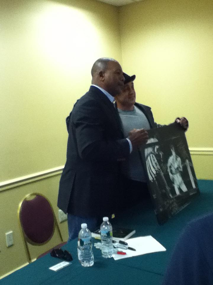 """My book (on the table) for The Champ, Apollo Cre-, I mean, the actor, Carl Weathers! (He also signed this picture, """"Ain't Gonna be No Rematch' I did of him and Stallone. He's upset I only painted his back side.)"""