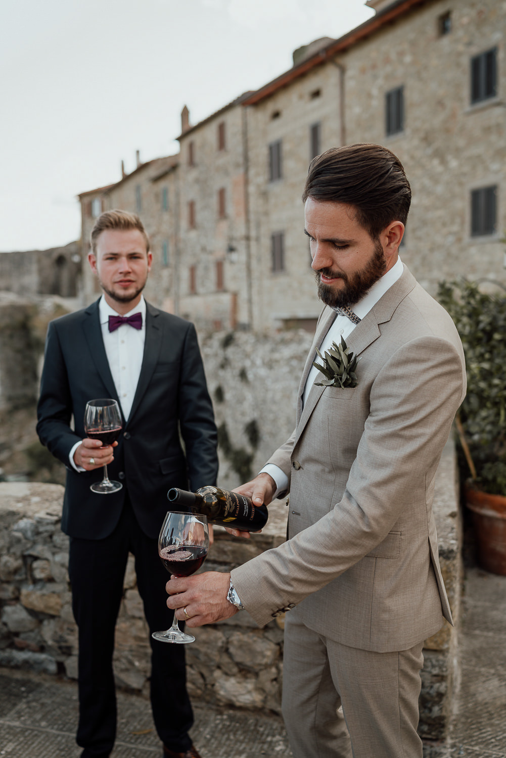 amsterdam wedding photography groom pours wine in tuscany at destination wedding