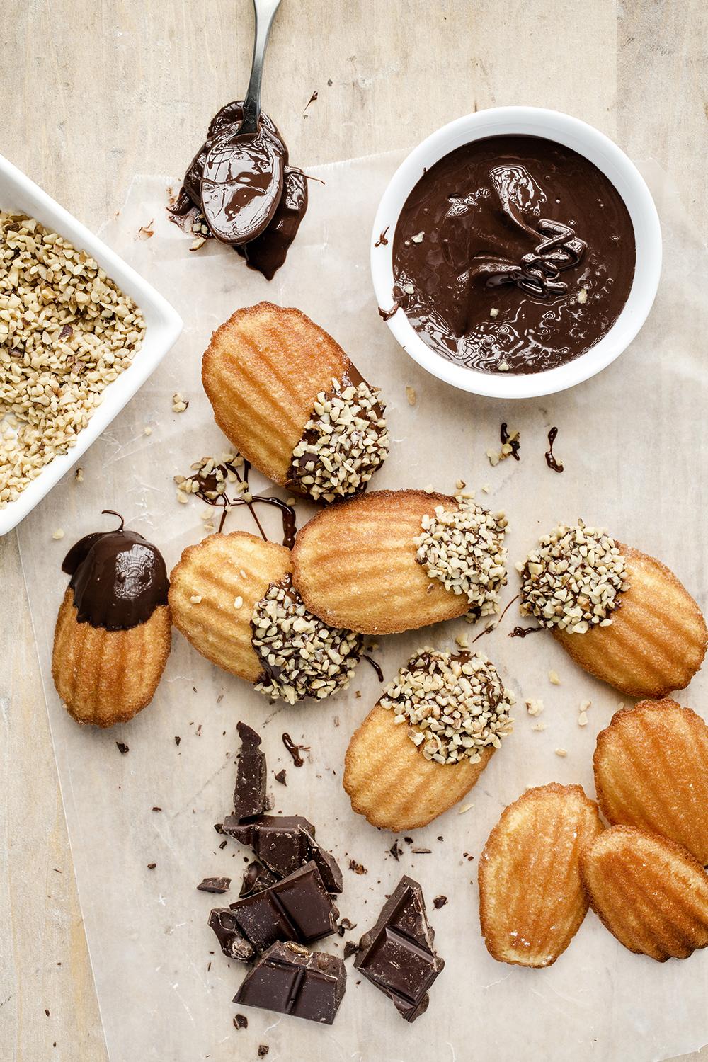 Madeleines coated in dark chocolate and crushed walnuts.