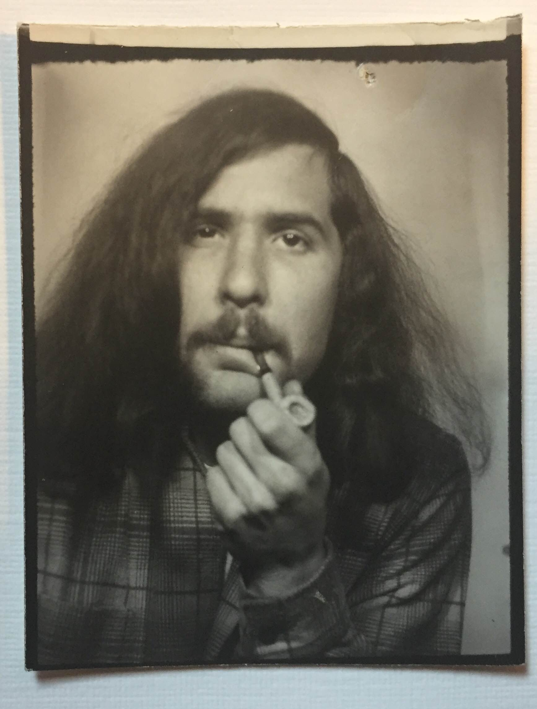 A section of a photo booth strip featuring my father and a pipe (c. 1975).
