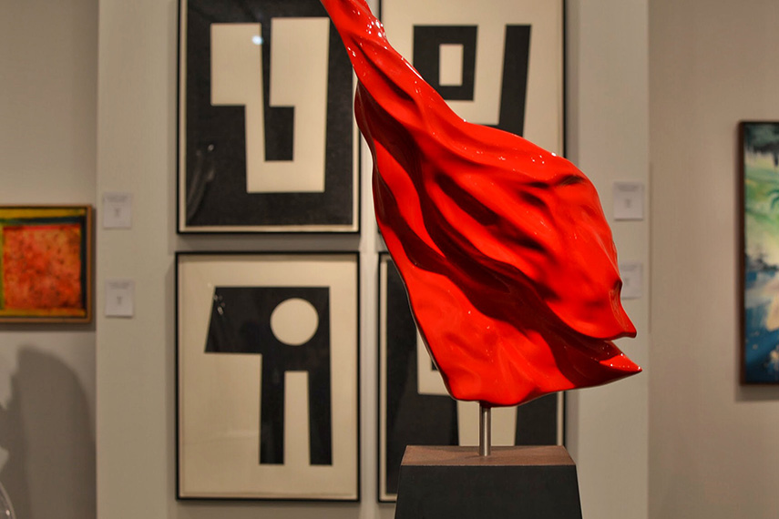 """This image features Santiago Medina's bright red sculpture """"Red Flame"""" and directly behind it John Guthrie's black and white abstract paintings from his Alternative Facts series. Frank Bowling's painting """"Tablet"""" can be seen to the far left. And to the far right, a small piece of Michael Albano's painting, """"Subsurface"""".   Photograph courtesy of Michelle VanTine Photography"""