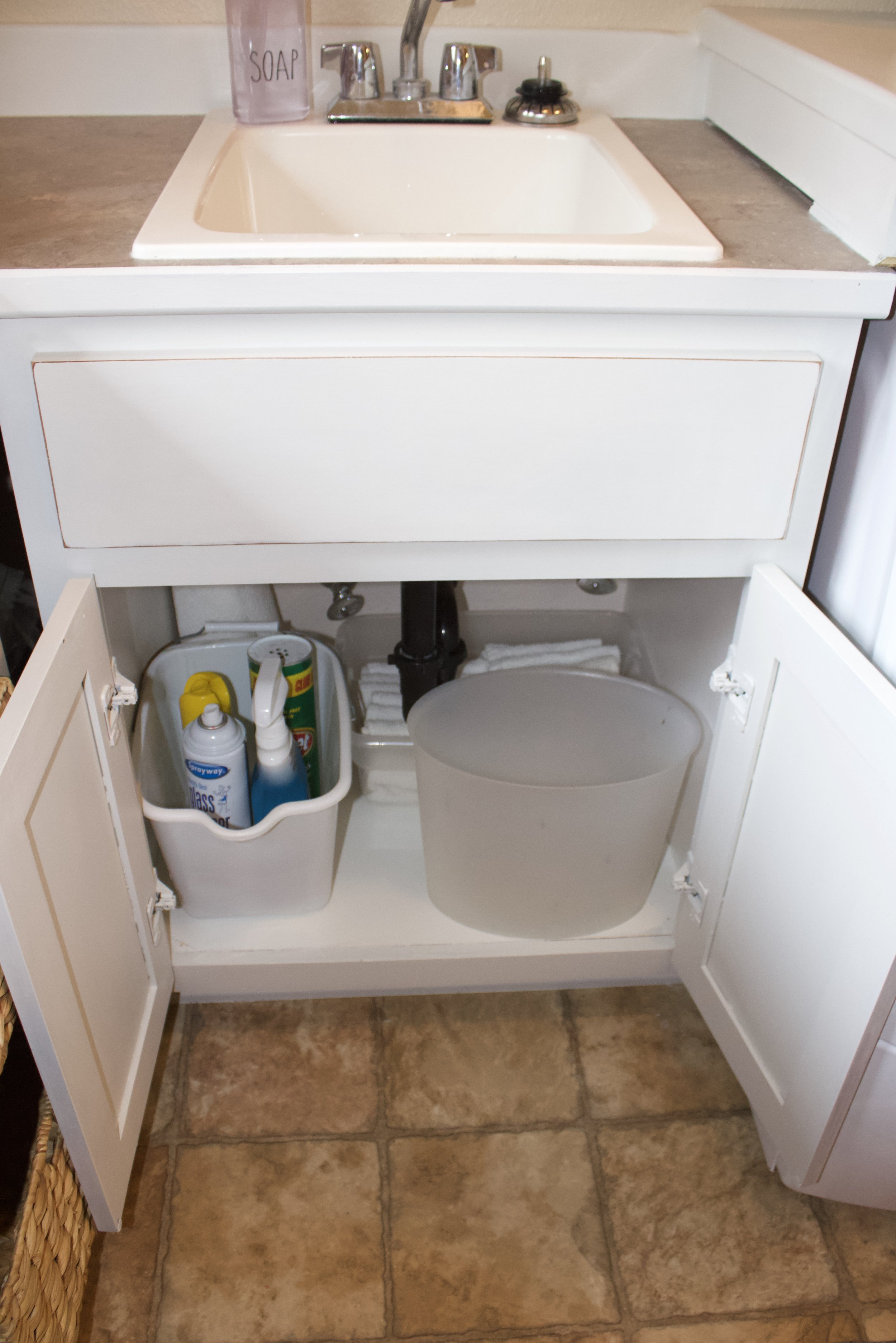 Under the sink is cleaning supplies, rags and a garbage can.