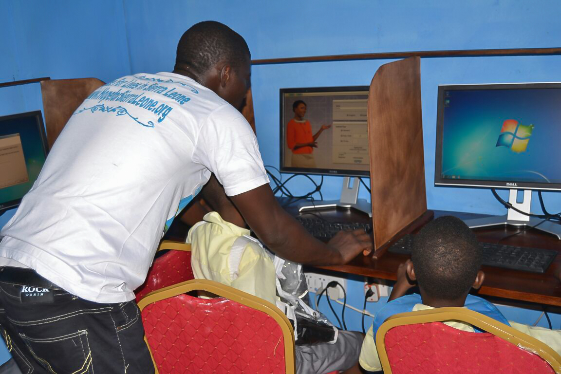 Our IT manager/computer trainer Kemoh Tarawally with teaching school kids