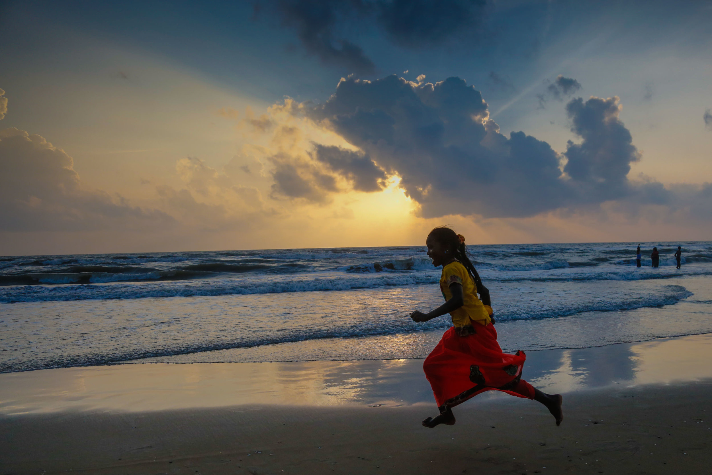 Gulf of Bengal, India:  a young pilgrim to Our Lady of Velankanni Shrine looks for seashells as the Sun rises on the Sea. Located in the state of Tamil Nadu, the Marian Shrine, called 'the Lourdes of the East receives 2 to 3 million pilgrims a year. Photo: Gustavo Kralj/GaudiumpressImages