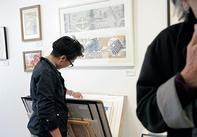 Visitor browsing prints at Lotte Arts and Tiny Splendor's pop-up at FFDG in June.