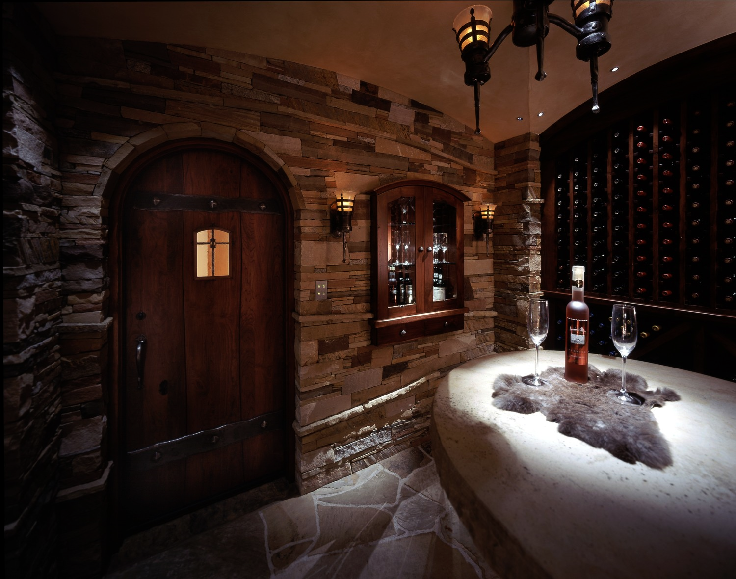 "Damien Cellar.  Hand crafted fiber optic ""flame"" sconces flank the internally Illuminated dessert wine cabinet while perfectly tuned white light Illuminates the tasting table."