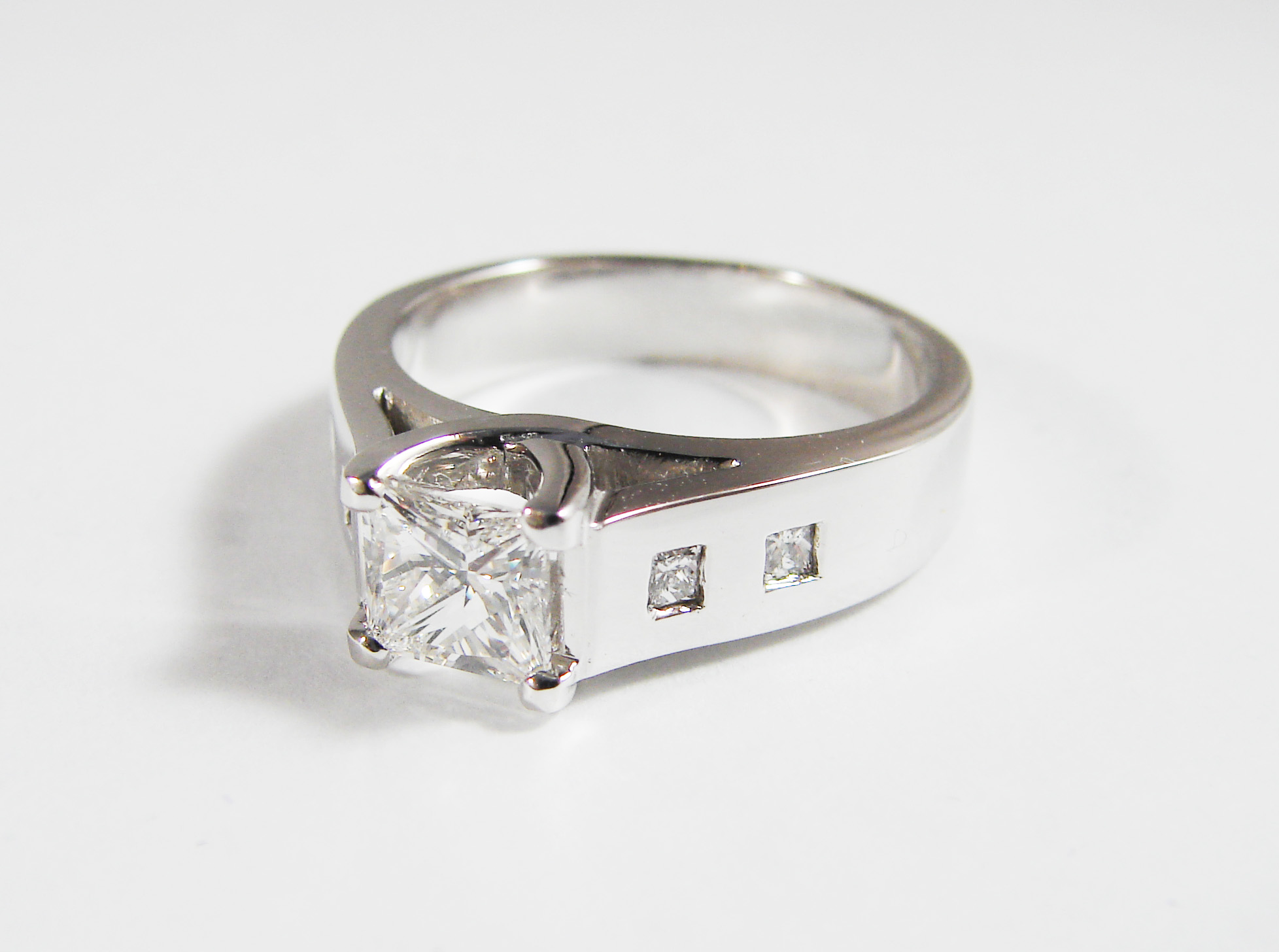 Princess cut 1.0ct diamond center stone, 0.28tcw diamond side stones, set in 14k white gold.  Starting at $6800 for this stone size  Can be customizable with any stone, size, metal etc.