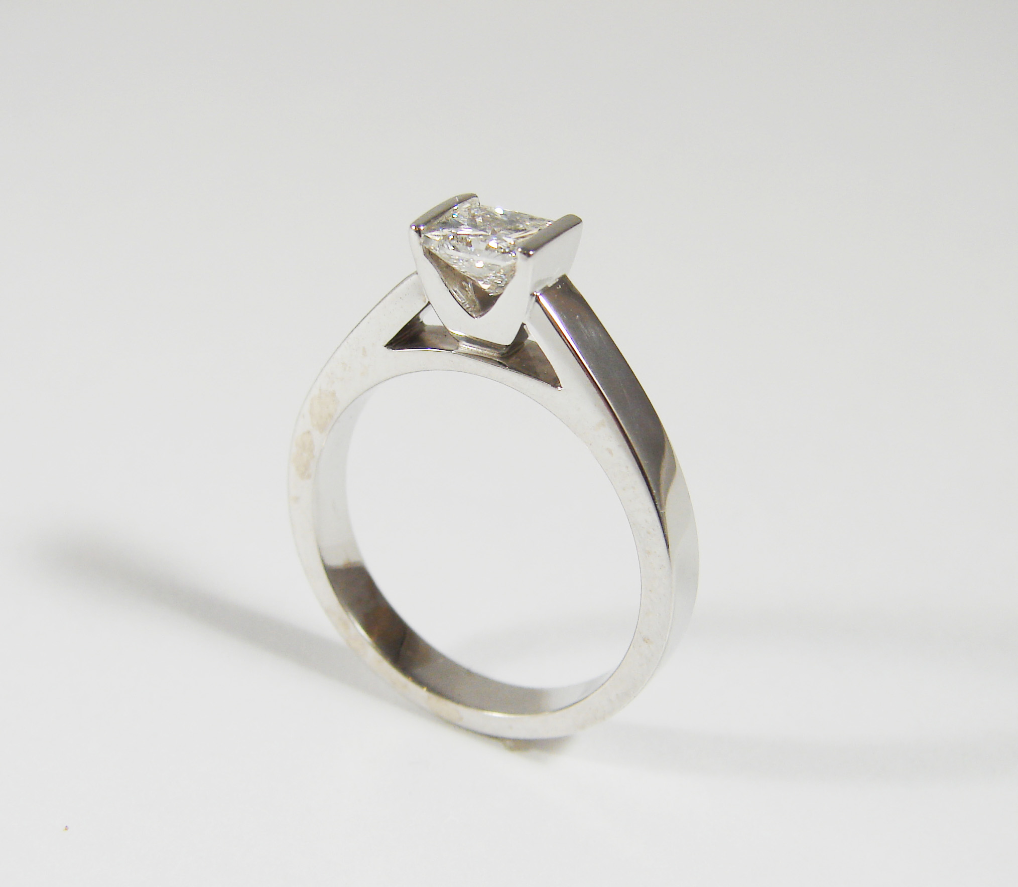 0.85ct princess cut diamond set in a V-shapedchannel setting, set in a flat 3.5mm wide shank that is in 14kt white gold.  Starting at $5600 for this stone size and quality  Can be customizable with any stone, size, metal etc.