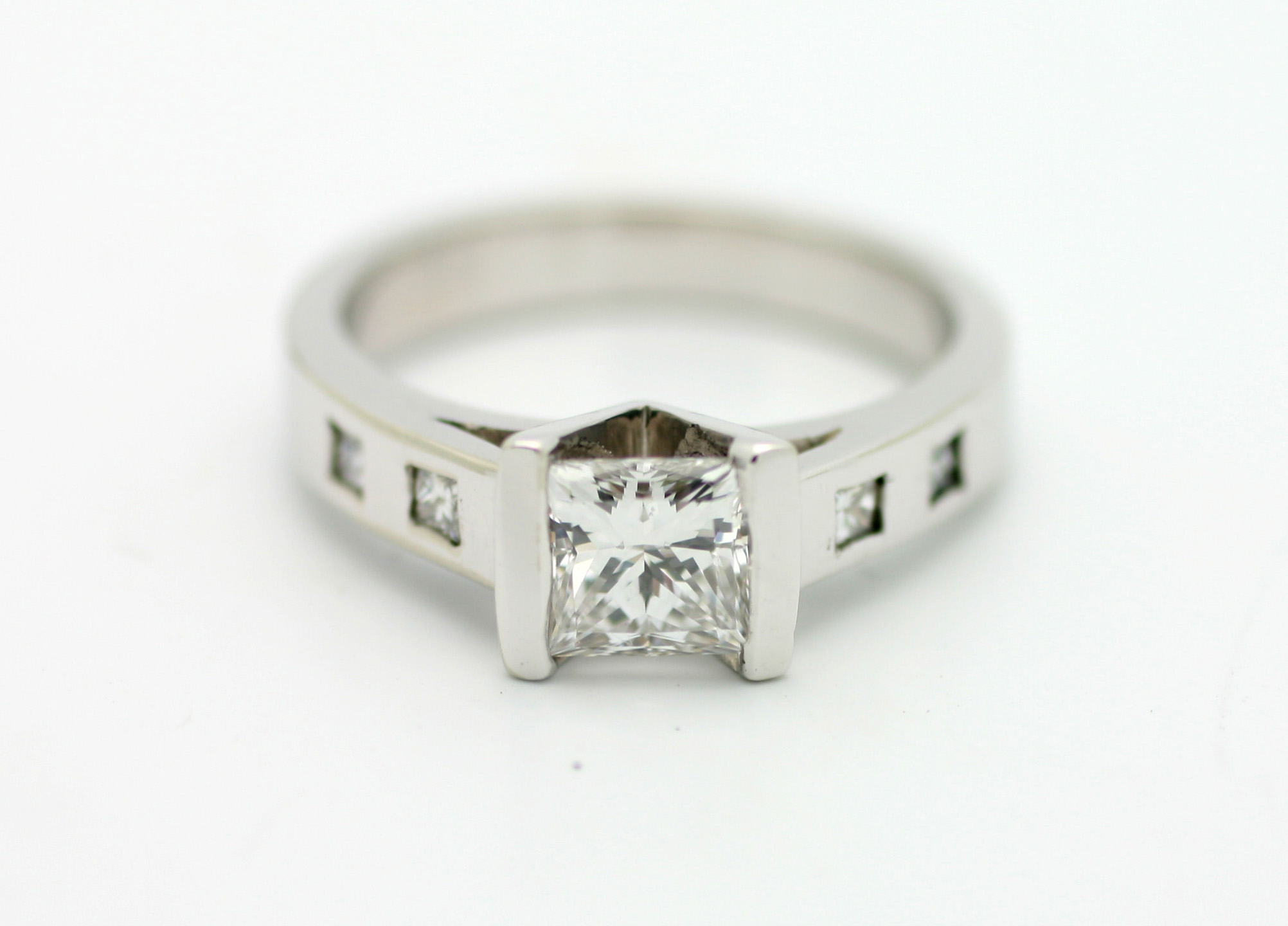 0.73ct princess cut diamond center stone set in a V-shape channel, shanks set with 4 gypsy set princess cut diamonds. 14kt white gold.  Starting at $4900 for this stone size and quality  Can be customizable with any stone, size, metal etc.