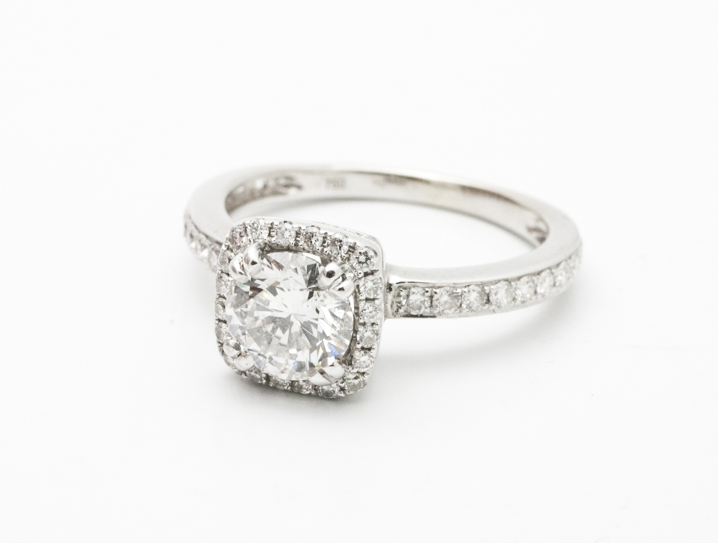 0.90ct round brilliant cut diamond cemtre stone surrounded by cushion shaped diamond halo,0.42tcw diamond side stones, 18kt white gold.  Starting at $7700 for this stone size and quality  Can be customizable with any stone, size, metal etc.