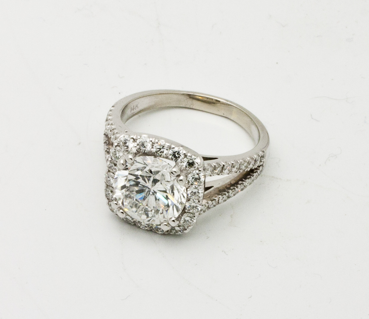 1.20ct round brilliant cut diamond center stone, 0.60tcw diamond side stones, cushion shaped diamond halo, split shank band, 18kt white gold.  Starting at $10,000 for this stone size and quality  Can be customizable with any stone, size, metal etc.