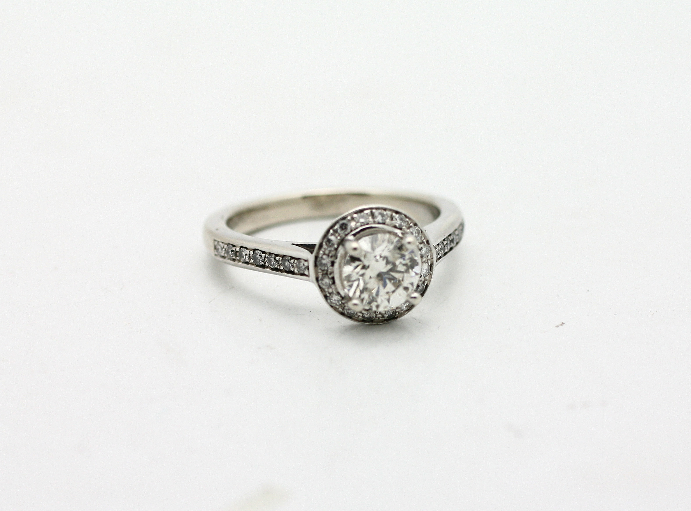 1.00ct round brilliant cut diamond center stone, surrounded with a small diamond halo. 0.30tcw diamond side stones, 18kt white gold.  Starting at $7000 for this stone size and SI-1 clarity GH colour  Can be customizable with any stone, size, metal etc.