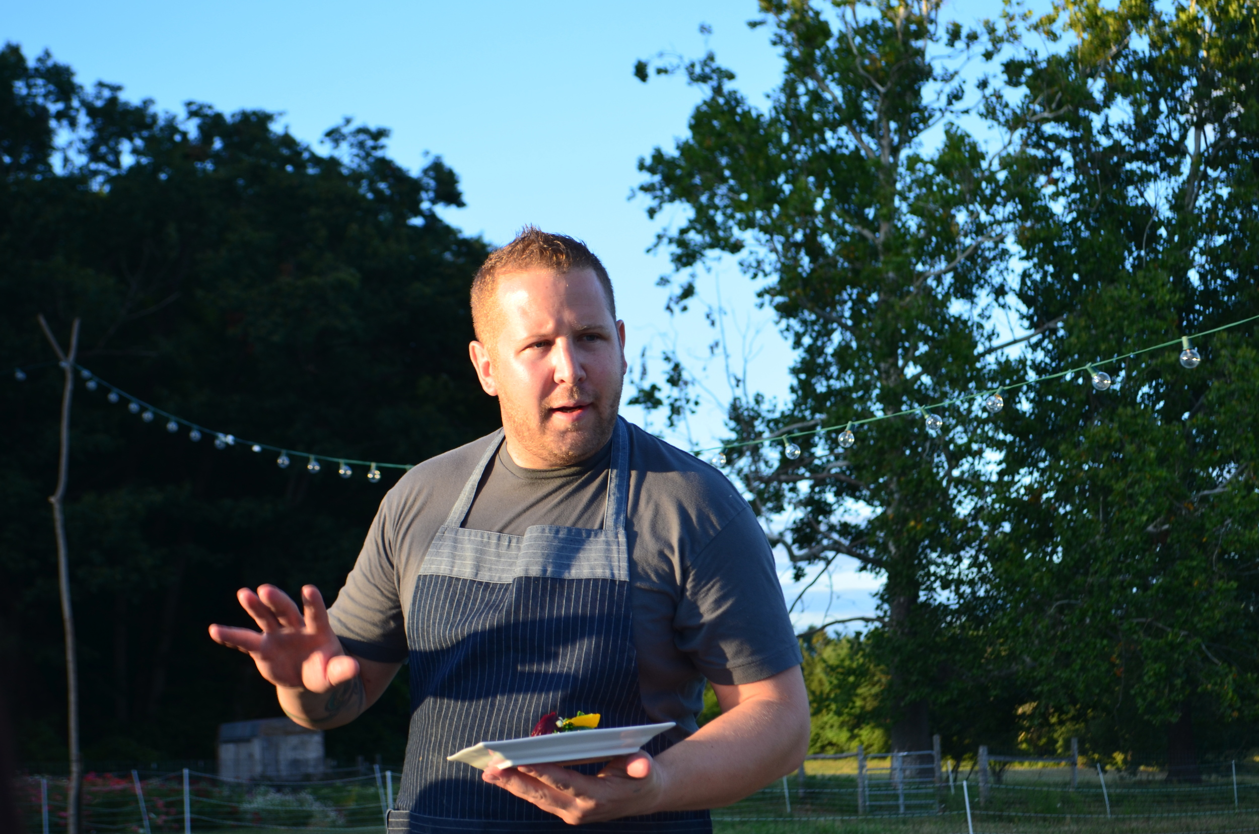 Chef Eric Stagl explaining the pork belly dish at Dinner in the Field at Eddy Farm