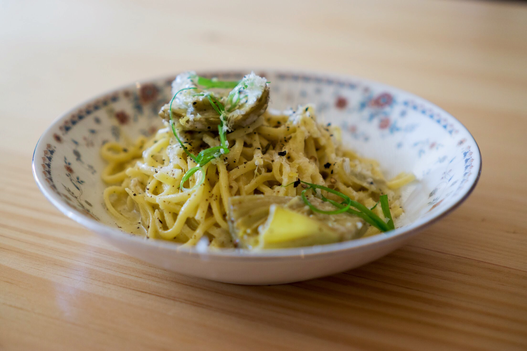 Spaghetti alla chitarra with preserved artichokes, aged cheese, smoked black pepper and scallions.  Photo by Alycia Chrosniak