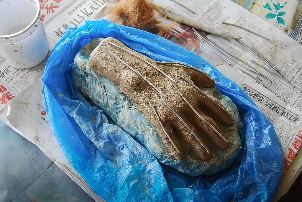 While the hand is still wet, metal pins are inserted as armature to further reinforce cohesiveness and structure. Here they are laid on top to gauge the right length. Behind the hand is a wad of reddish cow hair.