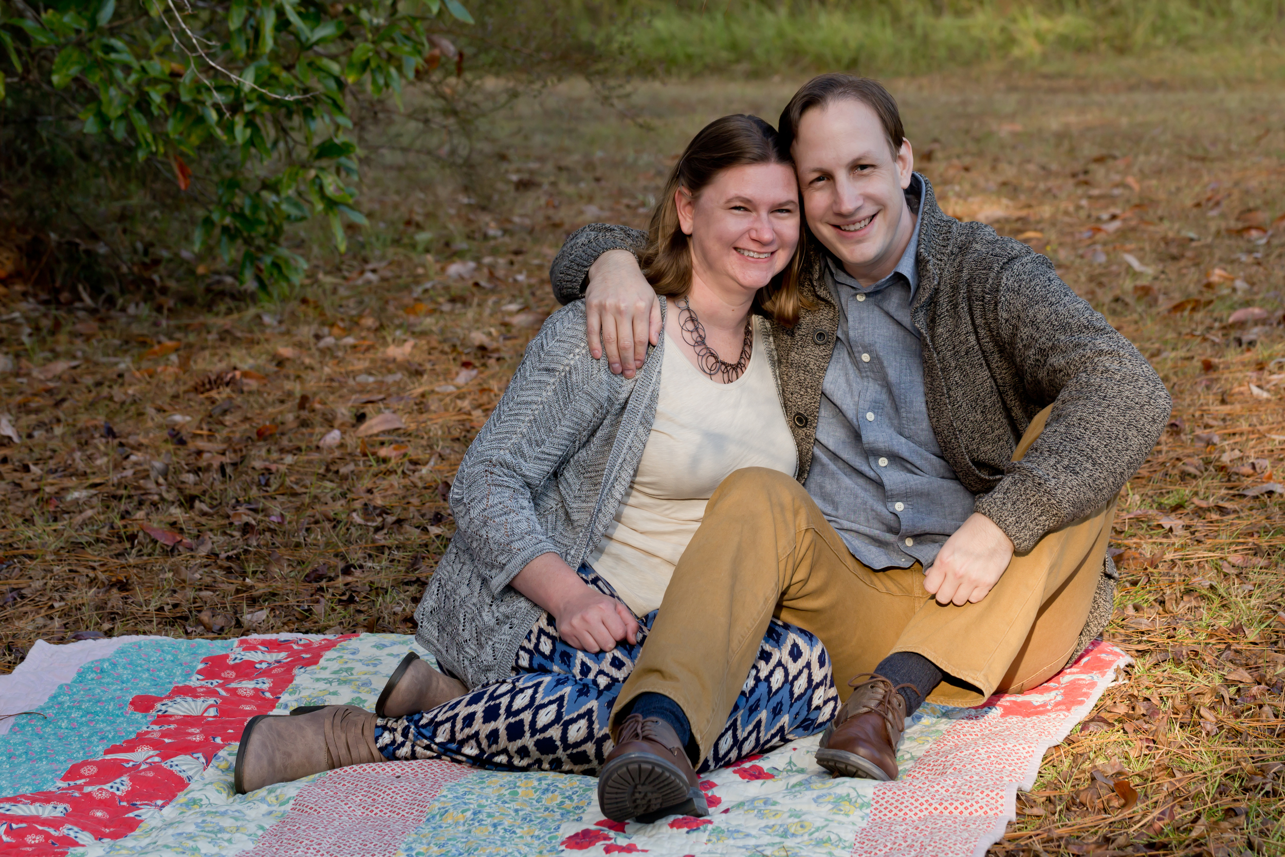 Engagement Photo with couple on vintage quilt outdoors (Uninvented Colors Photography)
