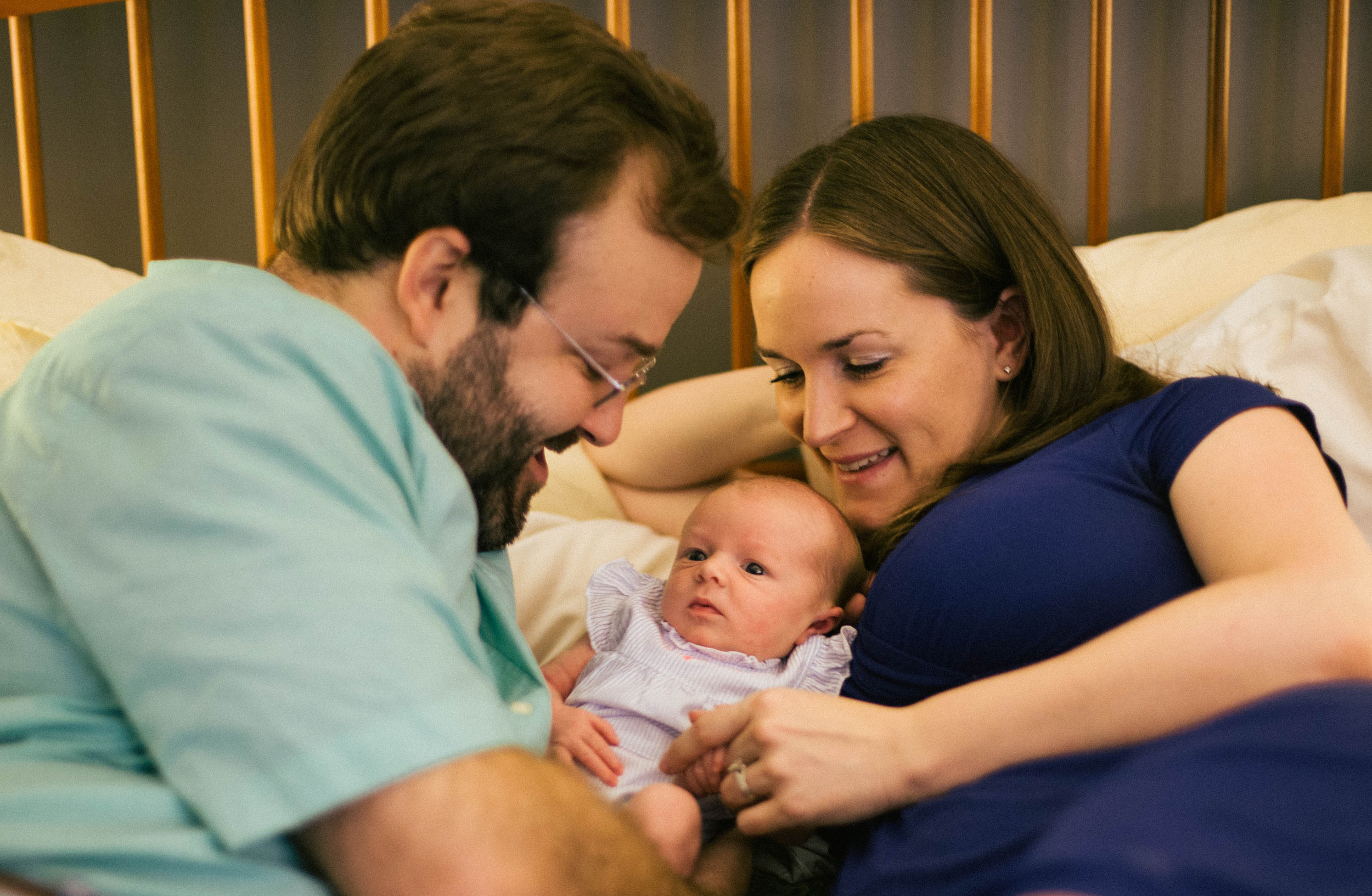 lifestyle newborn photo with parents and baby on bed