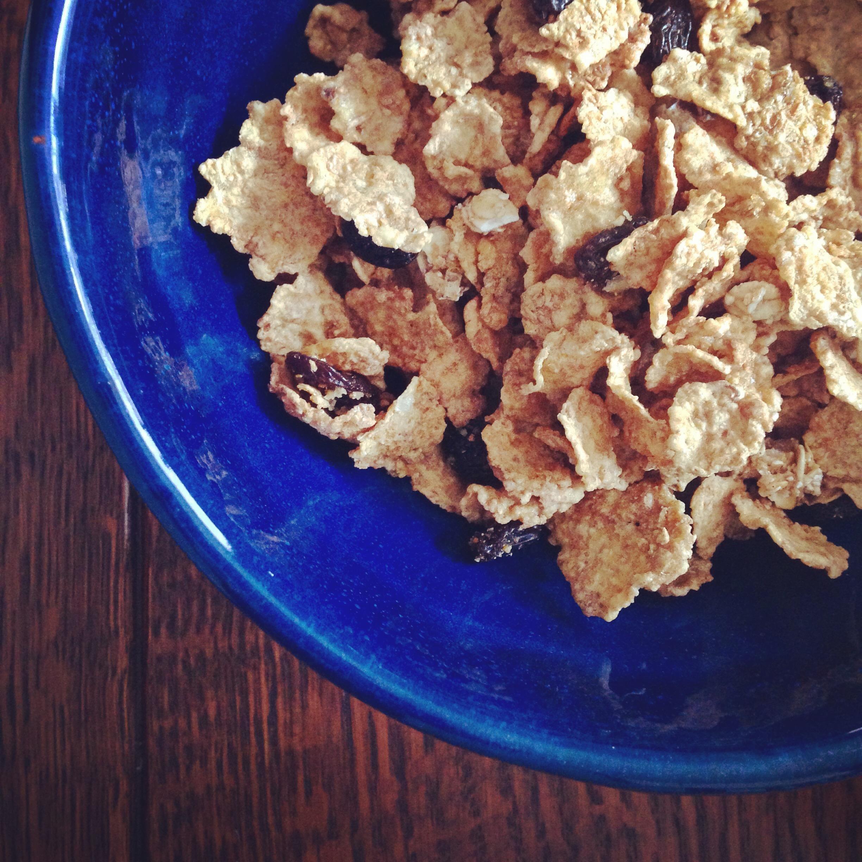 raisin bran in cobalt blue bowl on wooden table (breakfast cereal)