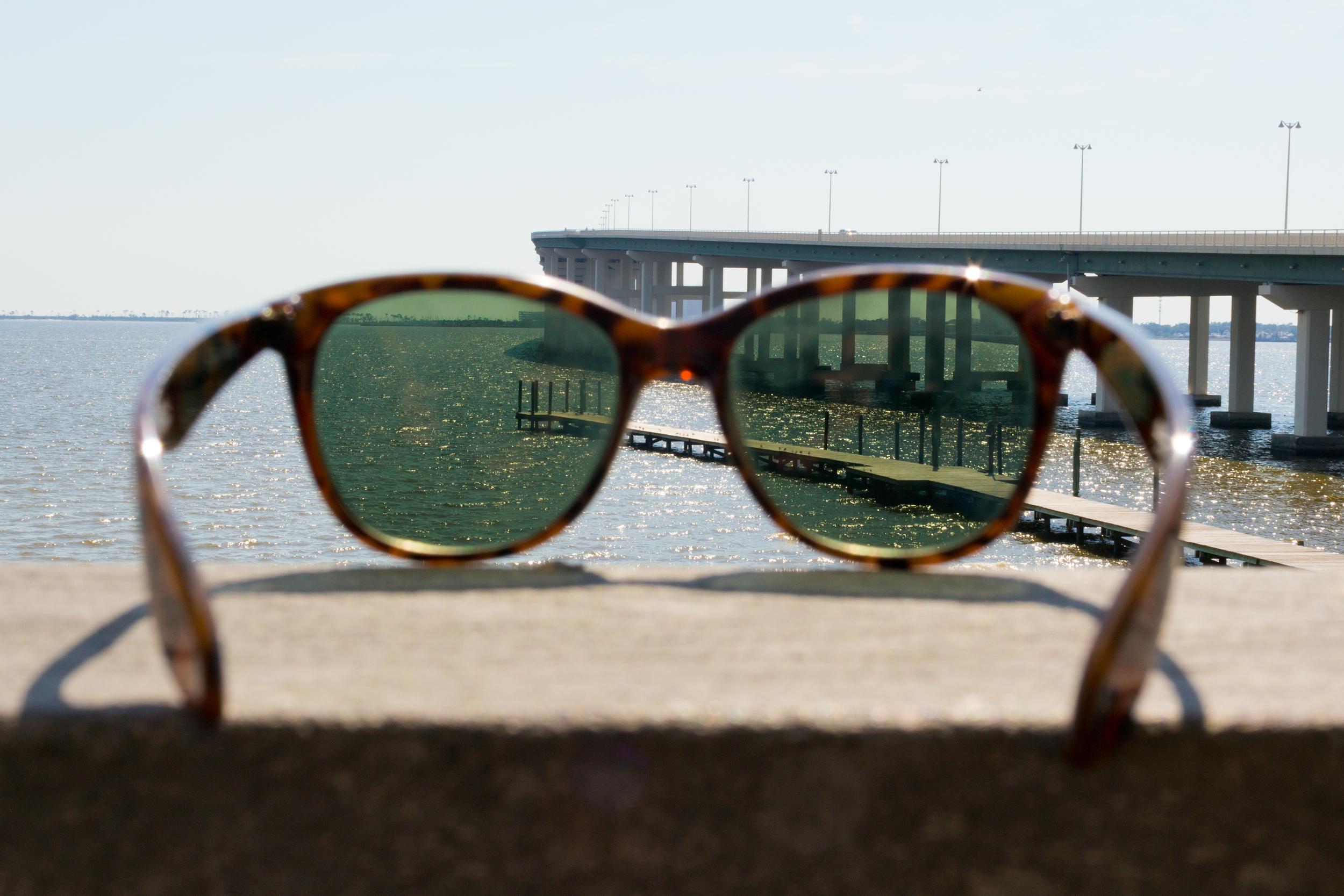 sunglasses with water, pier, bridge