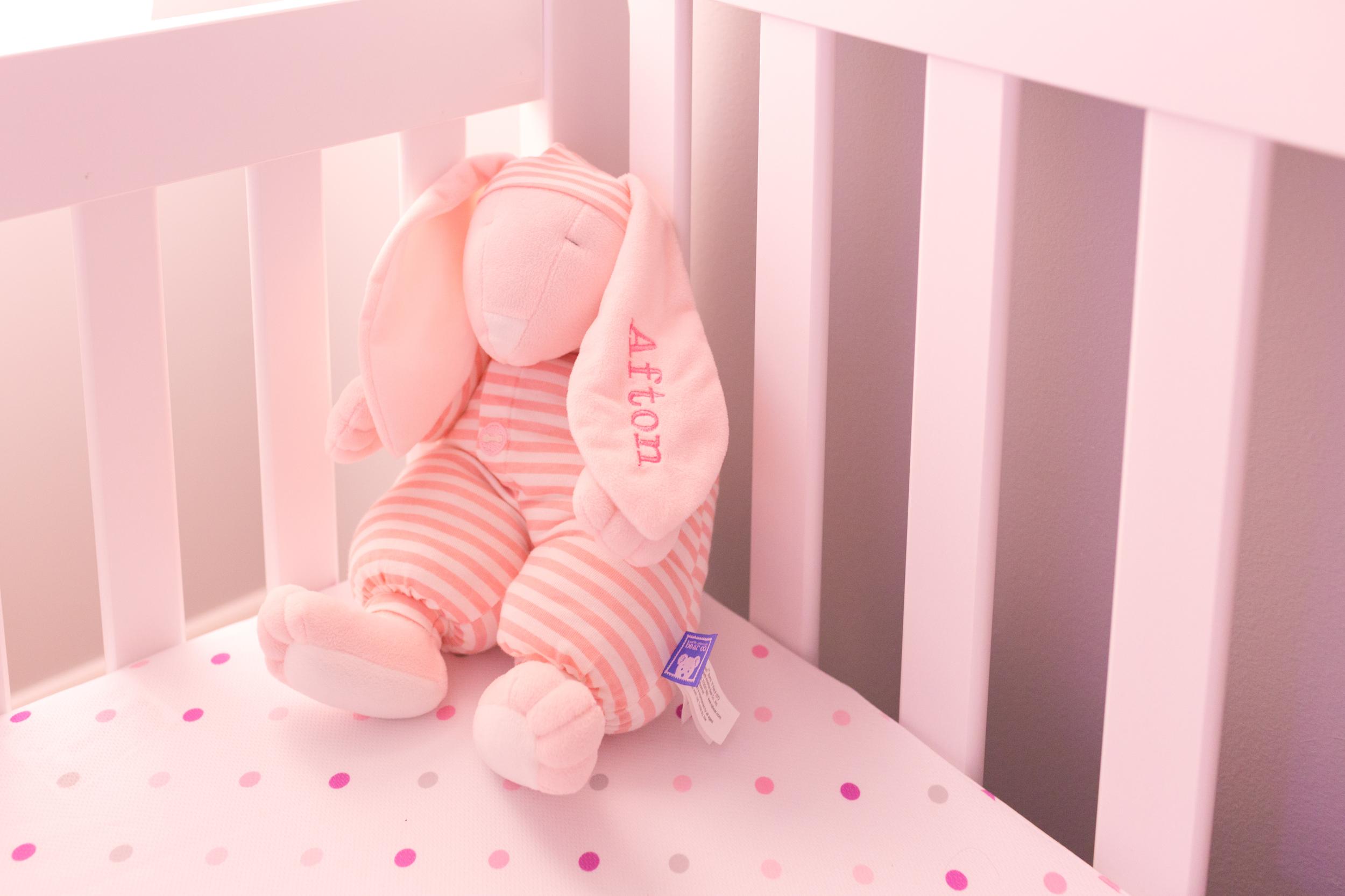 pink stuffed bunny rabbit for baby girl in crib