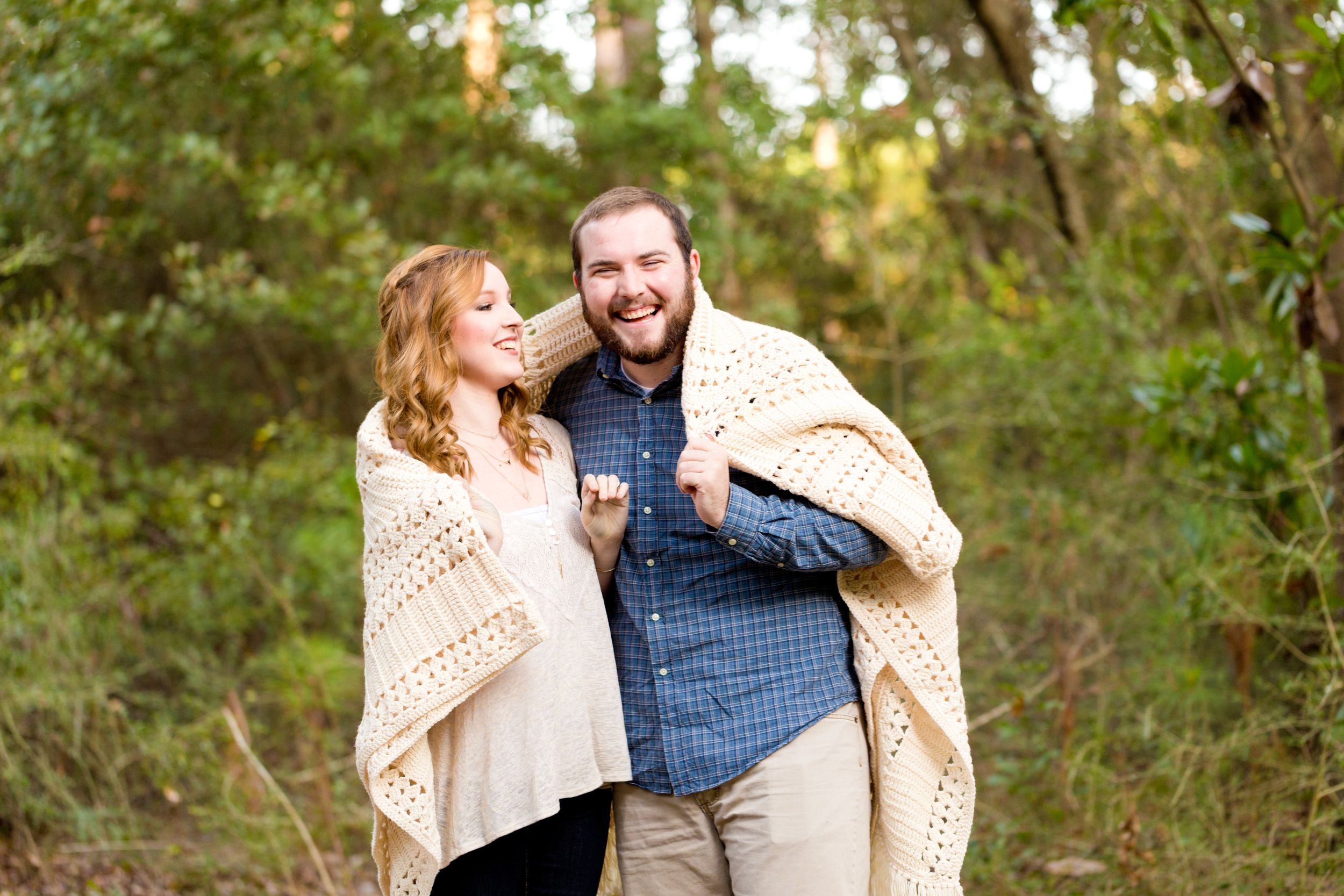 cute couple laughing wrapped in blanket outdoors
