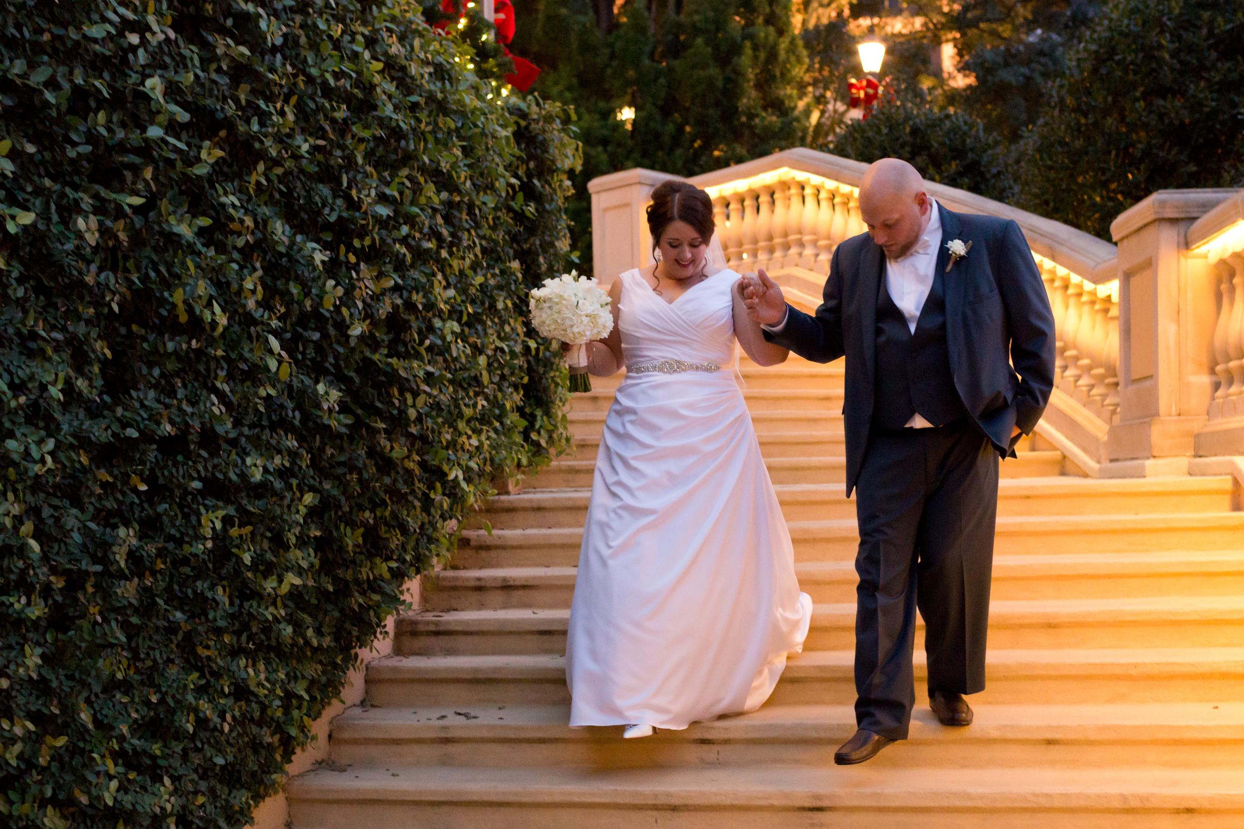 bride and groom walking down steps outside Beau Rivage (Biloxi wedding photo)