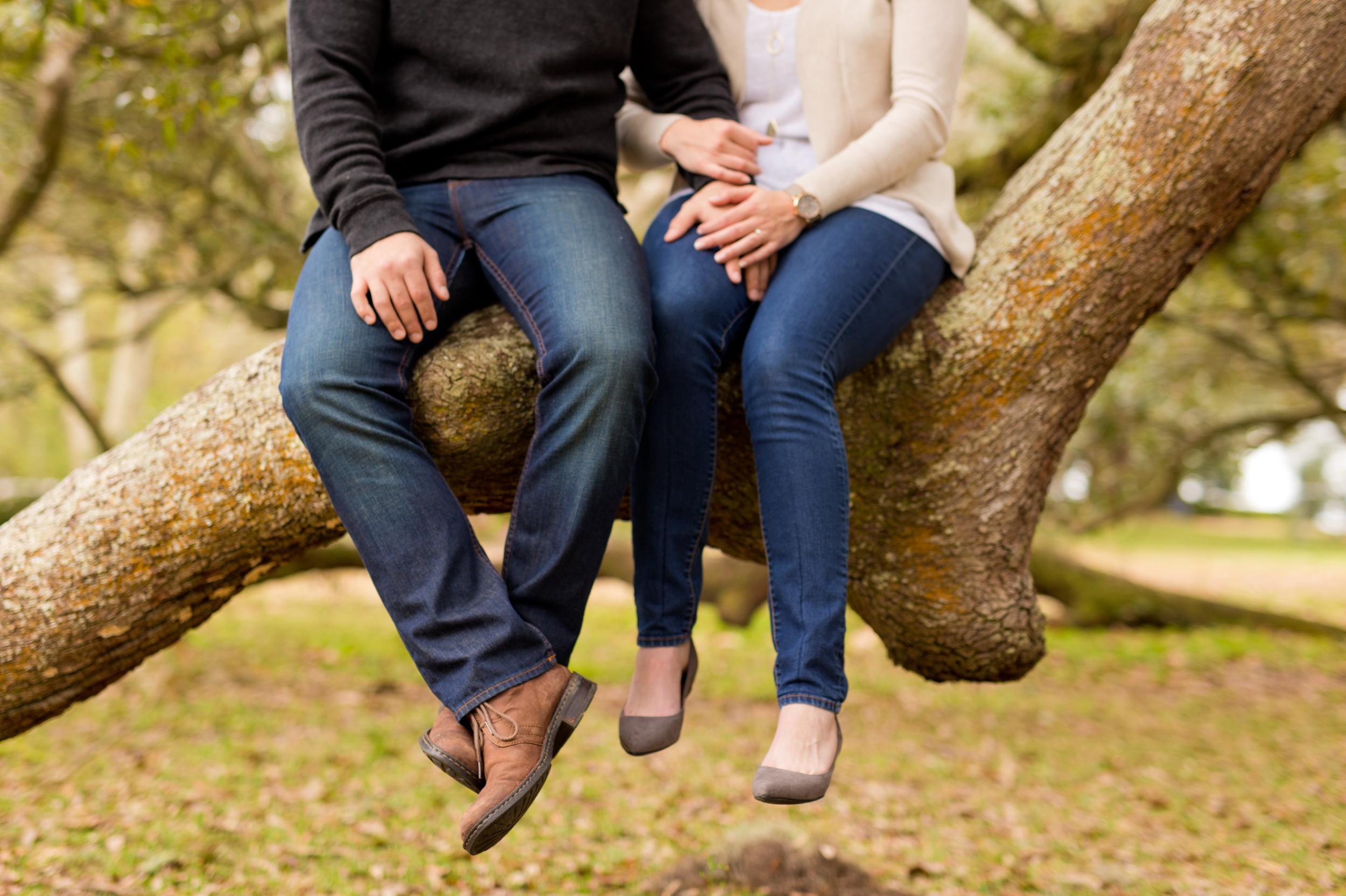 couple's feet and legs, sitting on live oak tree branch in denim blue jeans