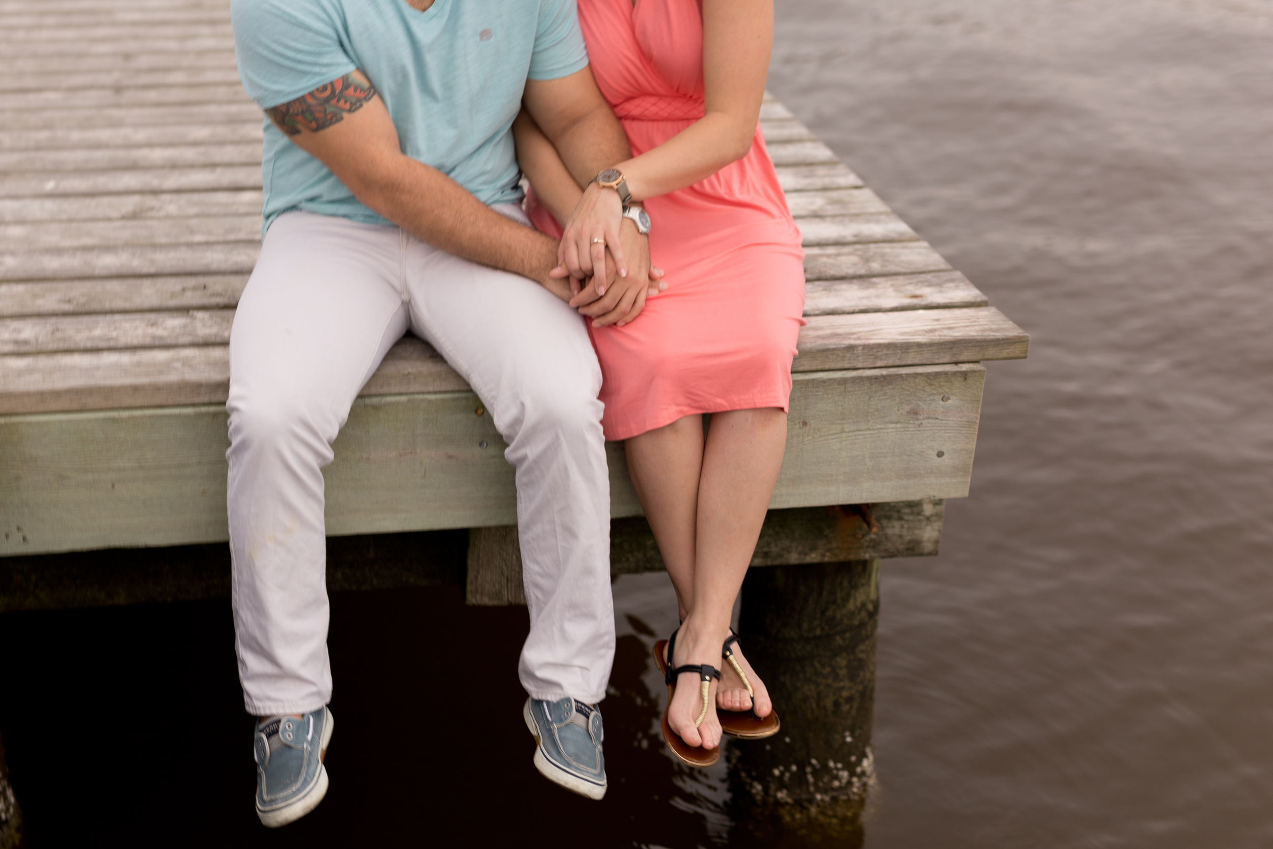 couple sitting on edge of dock in pastels
