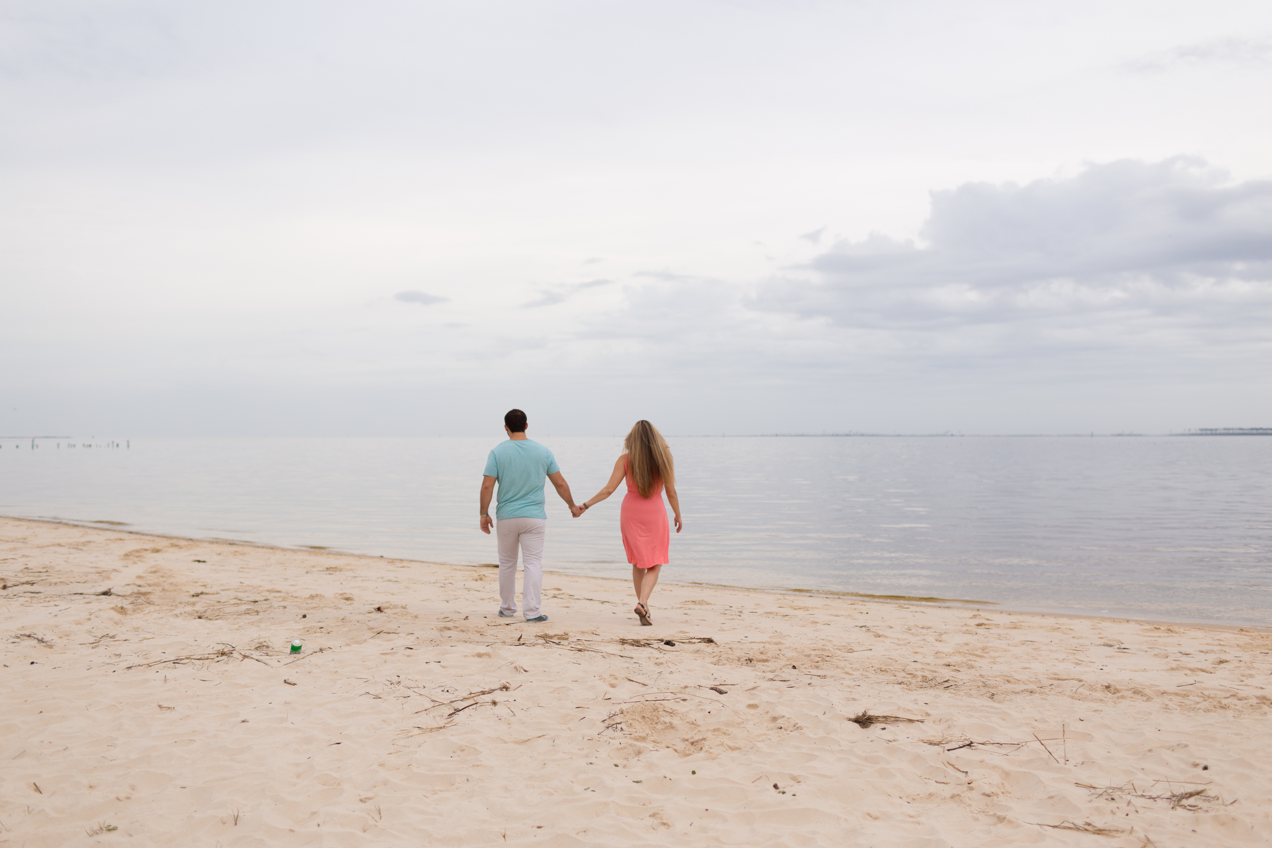 couple walking on beach holding hands on cloudy day