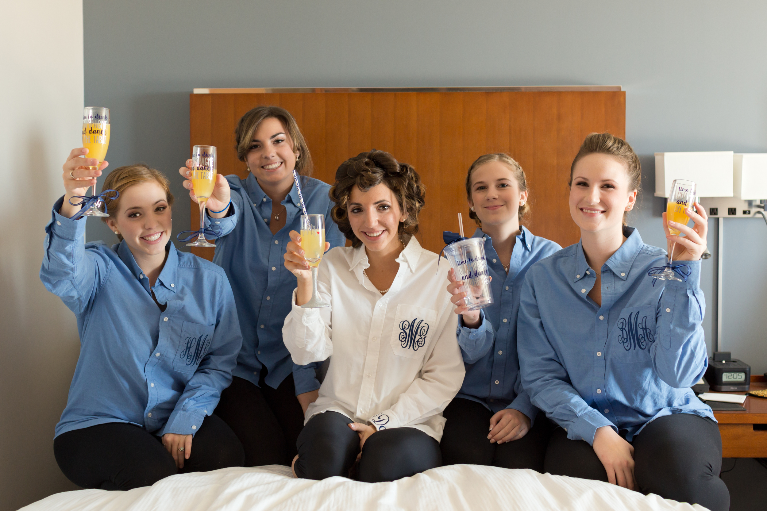 bride and bridesmaids in monogrammed shirts with mimosas